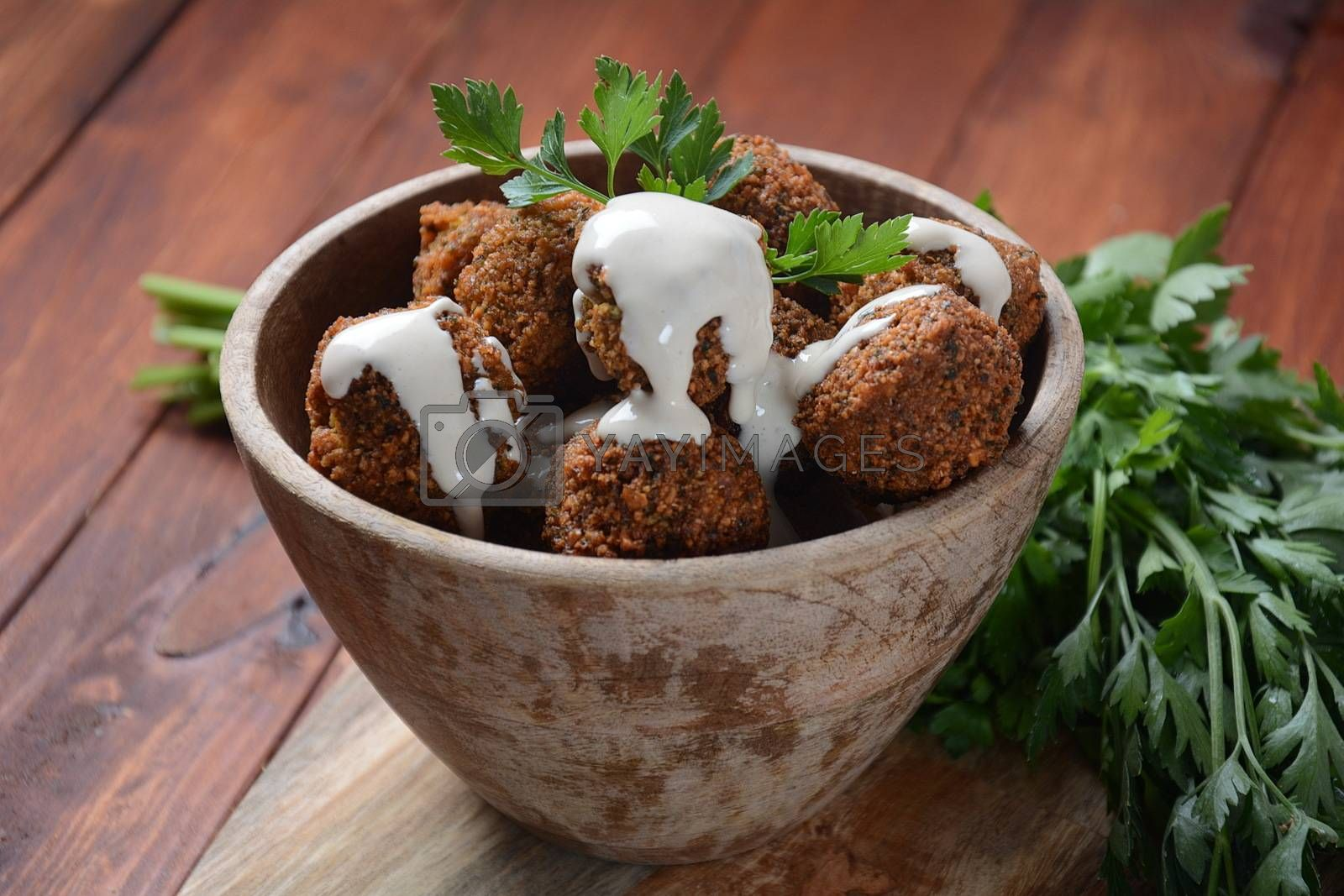 Falafel balls with parsley in wooden bowl with tahini sauce. Vegan healthy food