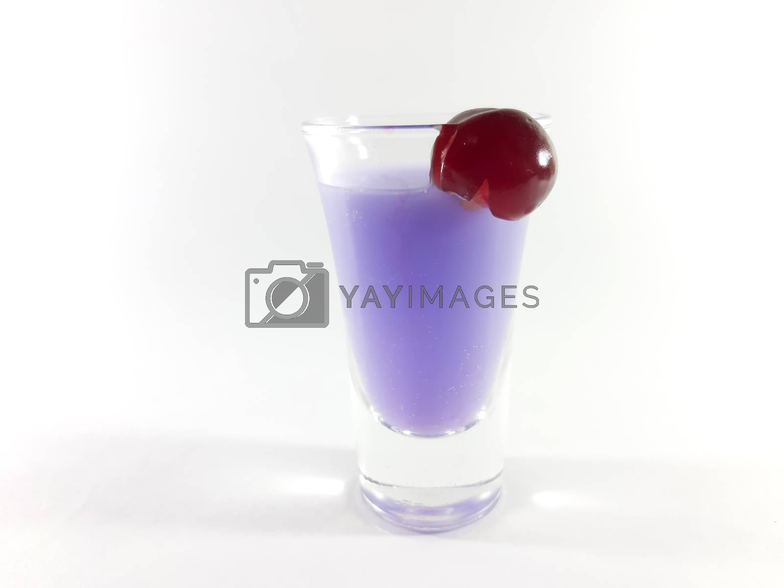Drink with fruit in transparent glass. Cherry for a snack. Violet liquid in a glass. Photo