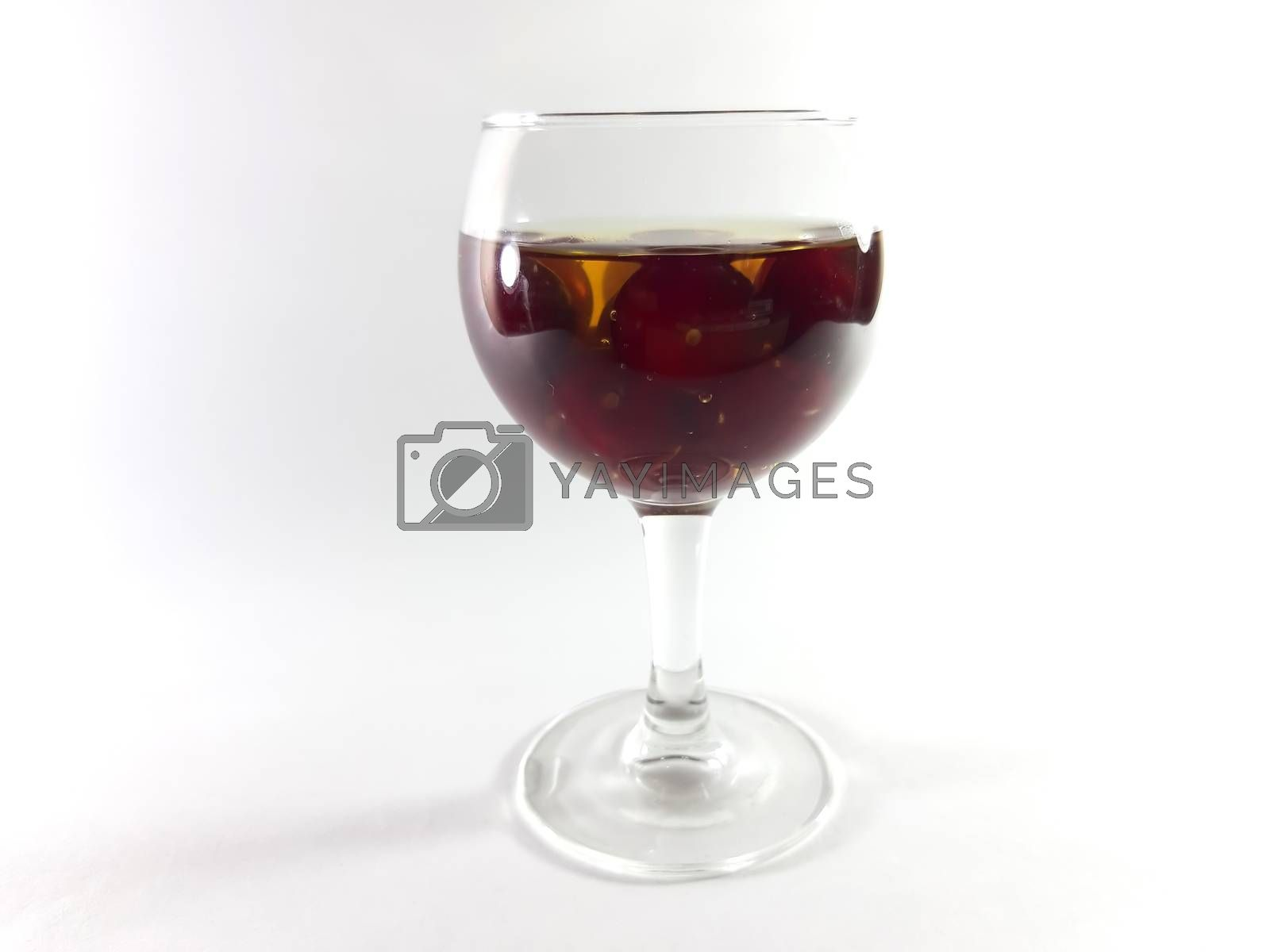 Drink with fruit in transparent glass. Cherry for a snack. Liquid in a glass. Photo isolated.
