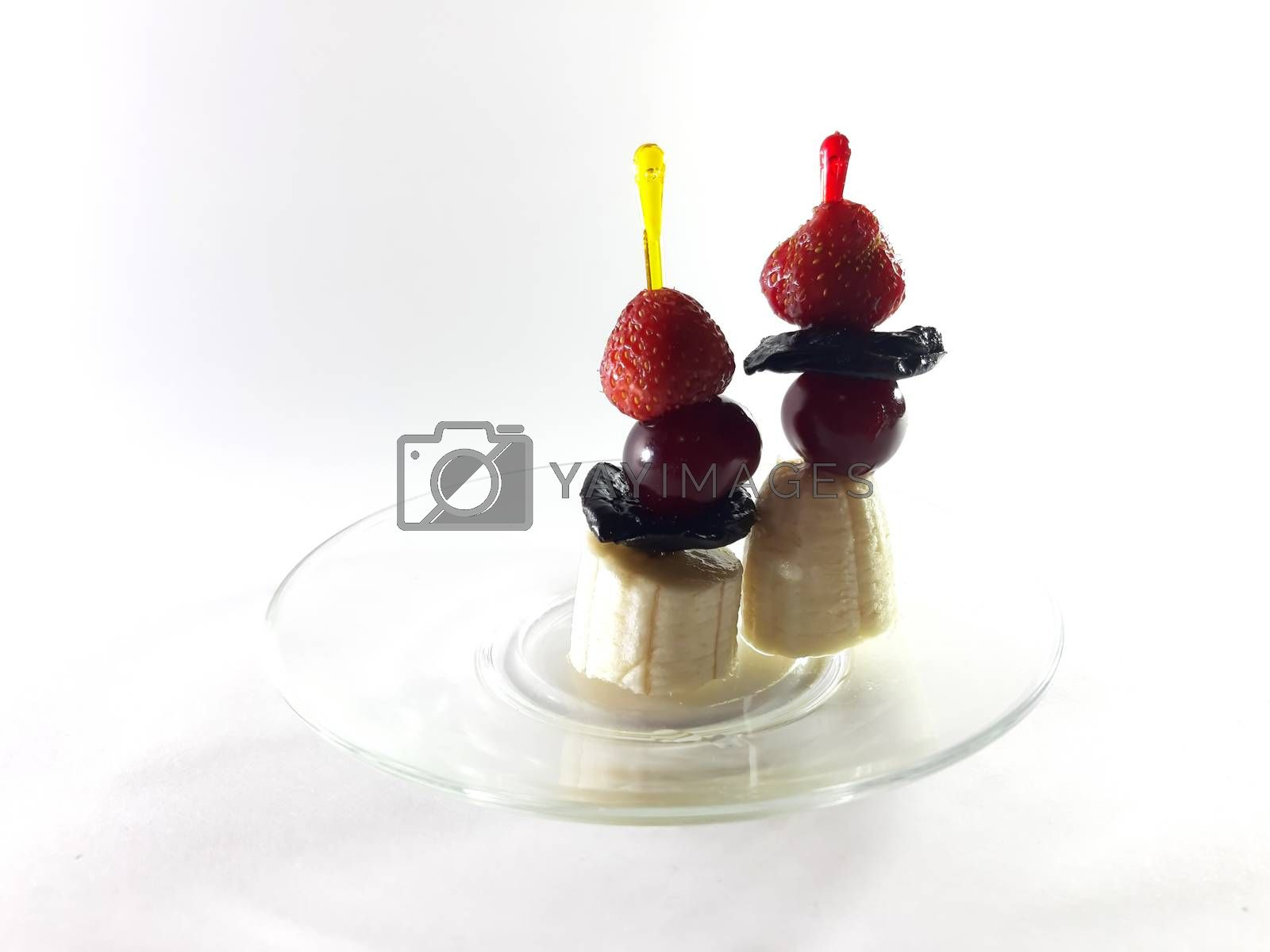 Dish for gourmet. Healthy food. Vegetarian foods on transparent plate. Berries and fruits. Lemon and cherry for a snack. Photo for modern design. Canapes made from bananas, strawberries and cherries.