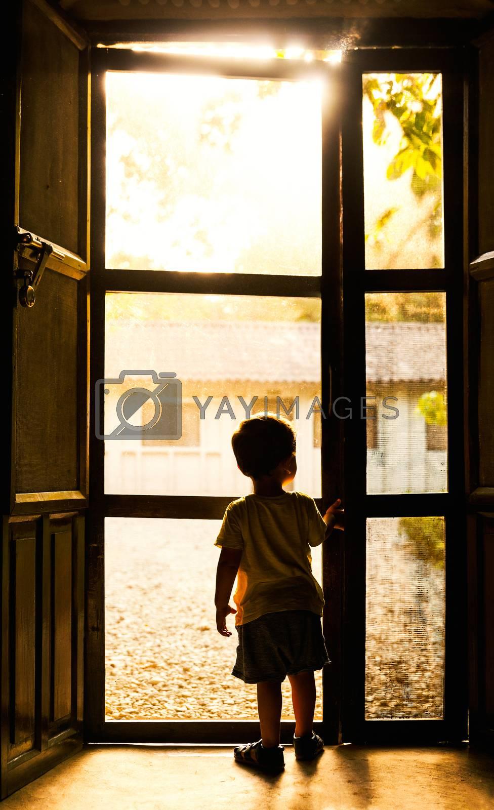 Backlit toddler standing in front of mosquito net door in Chitwan, Nepal