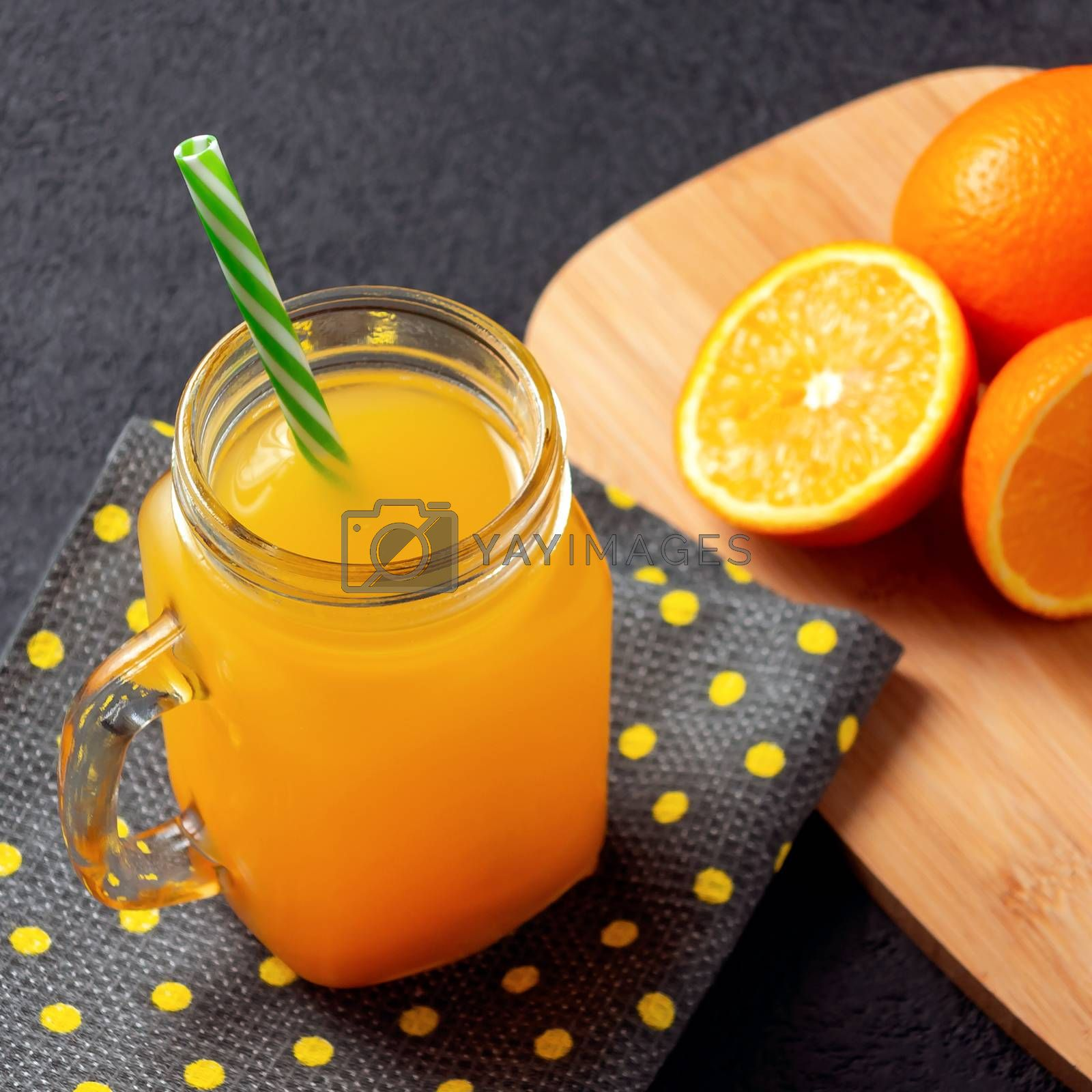 Freshly made citrus juice from oranges, grapefruit and lime in a jar-mug with a straw on black table by galsand