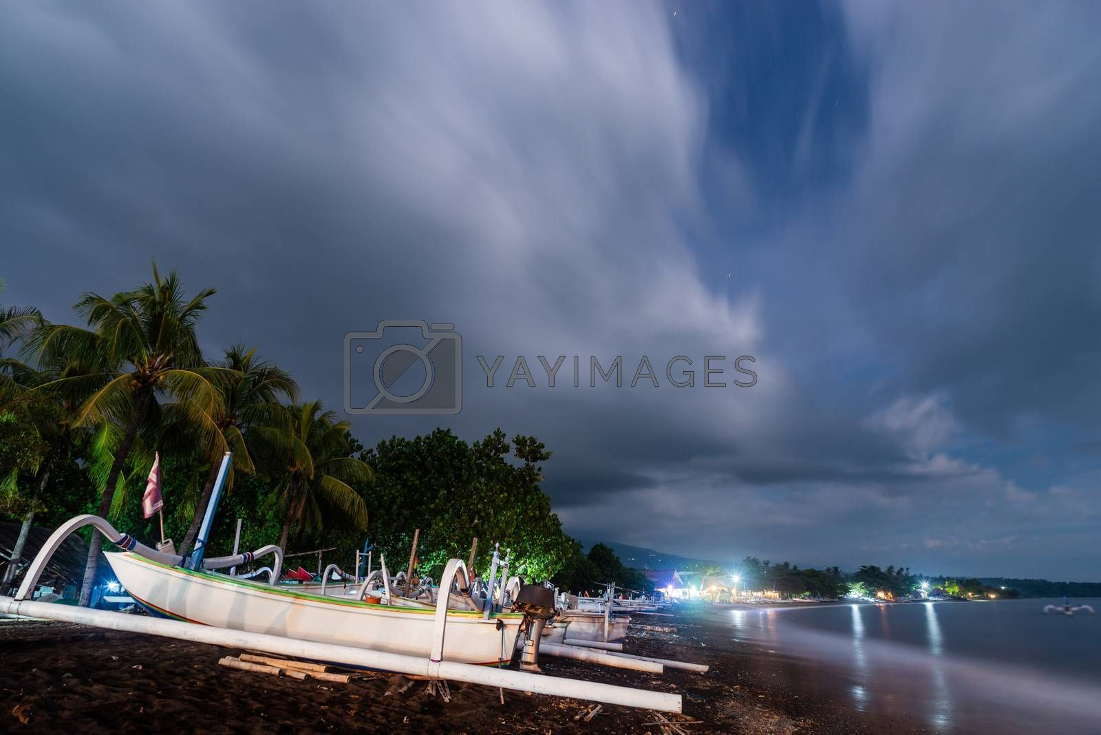 Traditional fishing boats on Amed beach at night in Bali, Indonesia. Long exposure photography resulting in motion blur in the clouds, the sea and the trees.