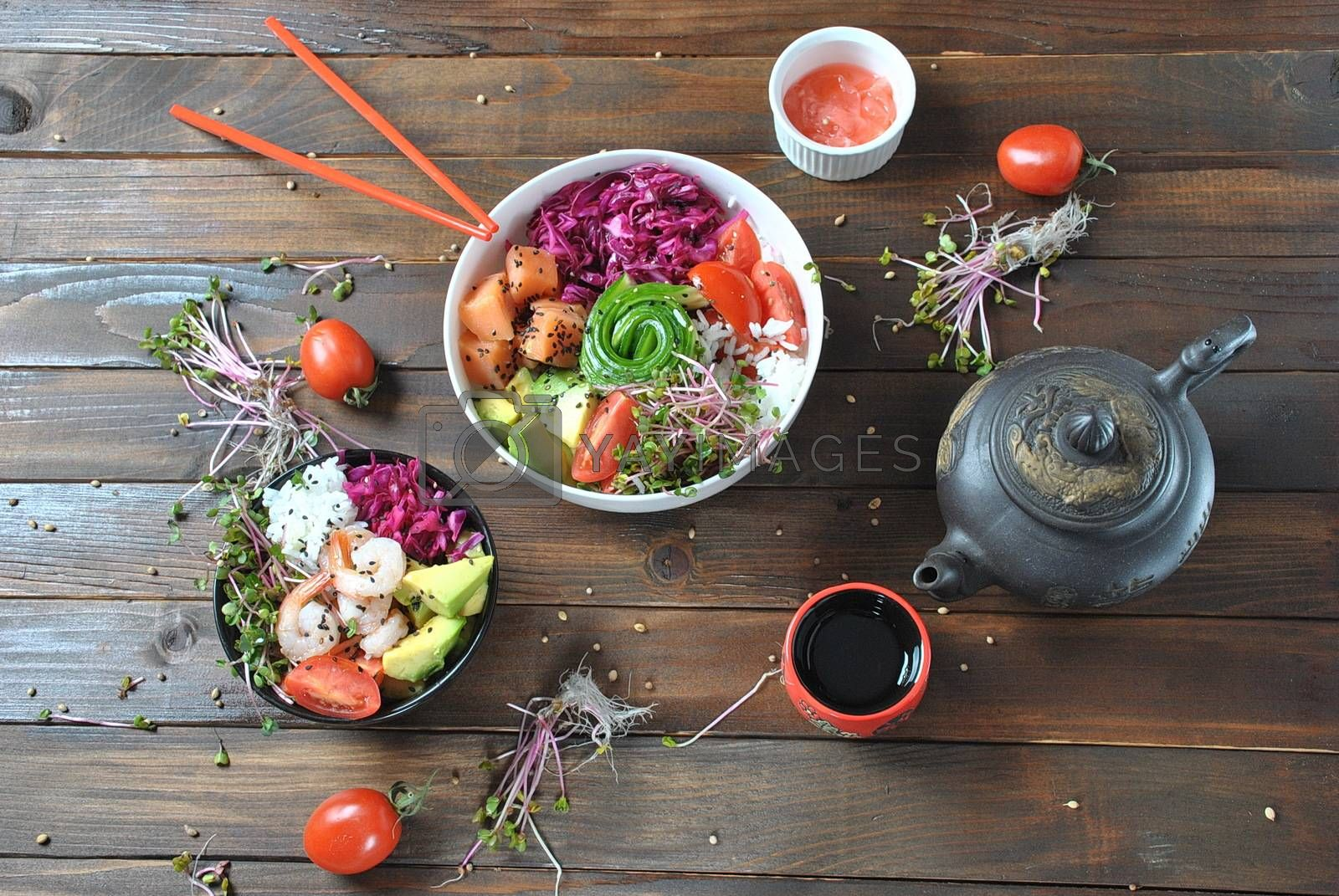 Organic food. Fresh seafood recipe. Two fresh poke bowls with salmon, shrimps, rice, red cabbage, avocado, cherry tomatoes and radish sprouts on wooden background. Food concept Poke Bowl