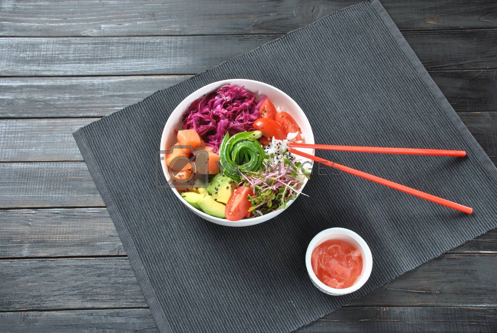 Organic food. Fresh seafood recipe. fresh poke bowl with salmon,  rice, red cabbage, avocado, cherry tomatoes and radish sprouts on wooden background. Food concept Poke Bowl