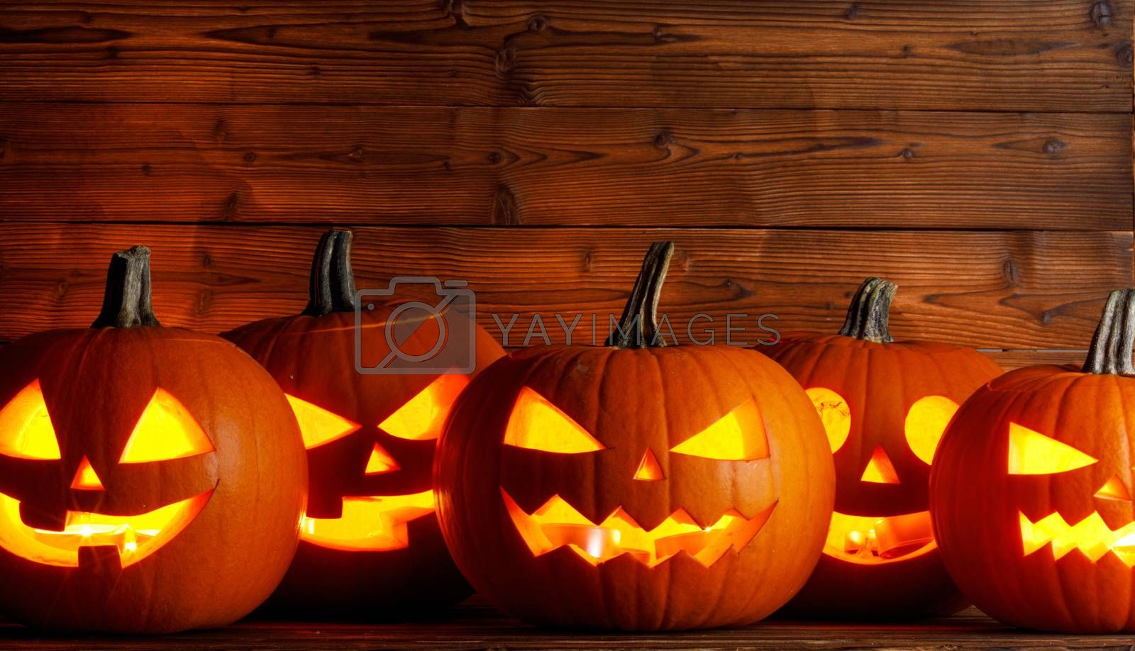 Glowing Halloween pumpkins head jack o lantern on wooden background