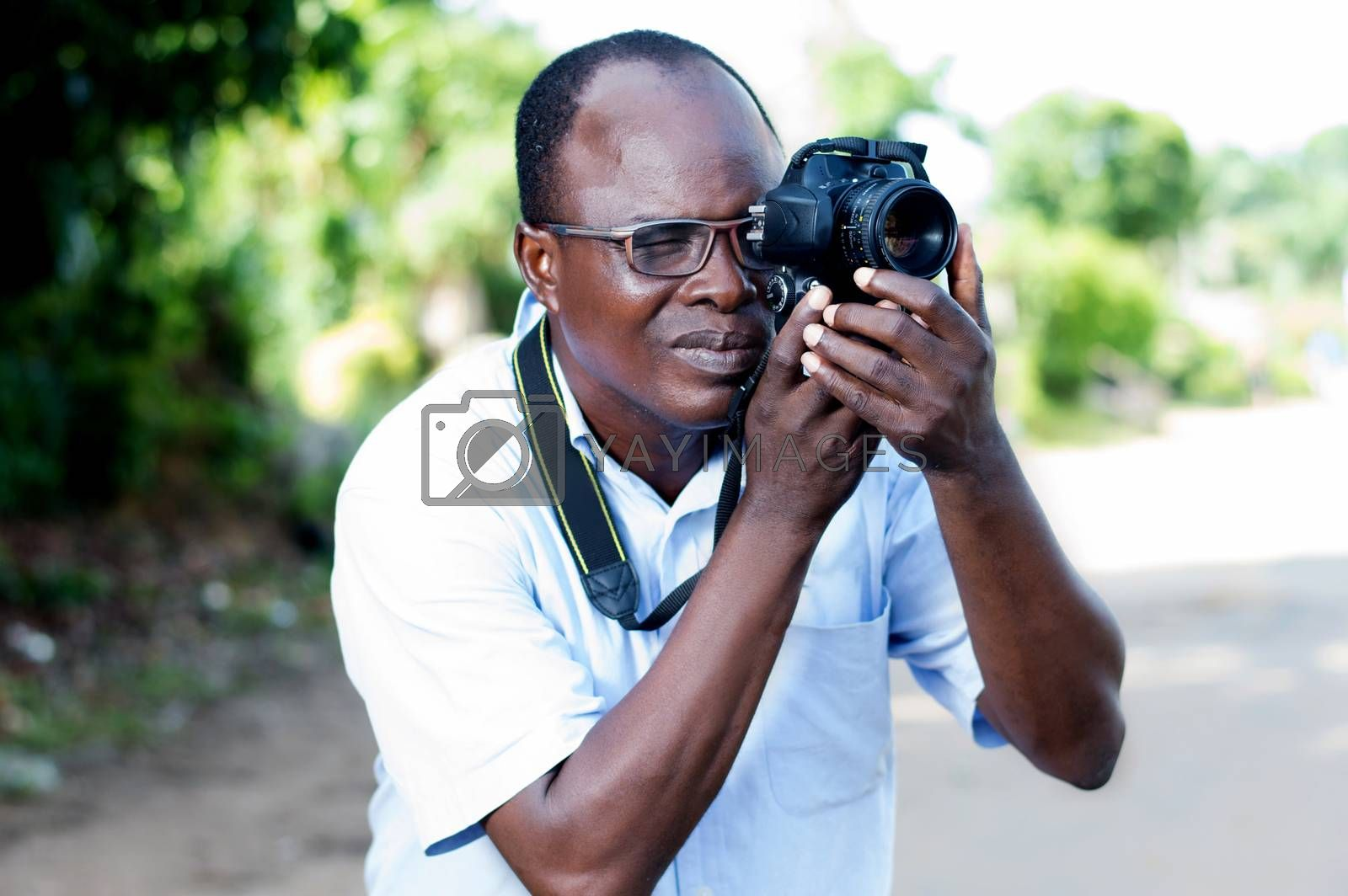 people, photography, entertainment and lifestyle - happy young man holding a digital camera and taking pictures on the street of the campaign