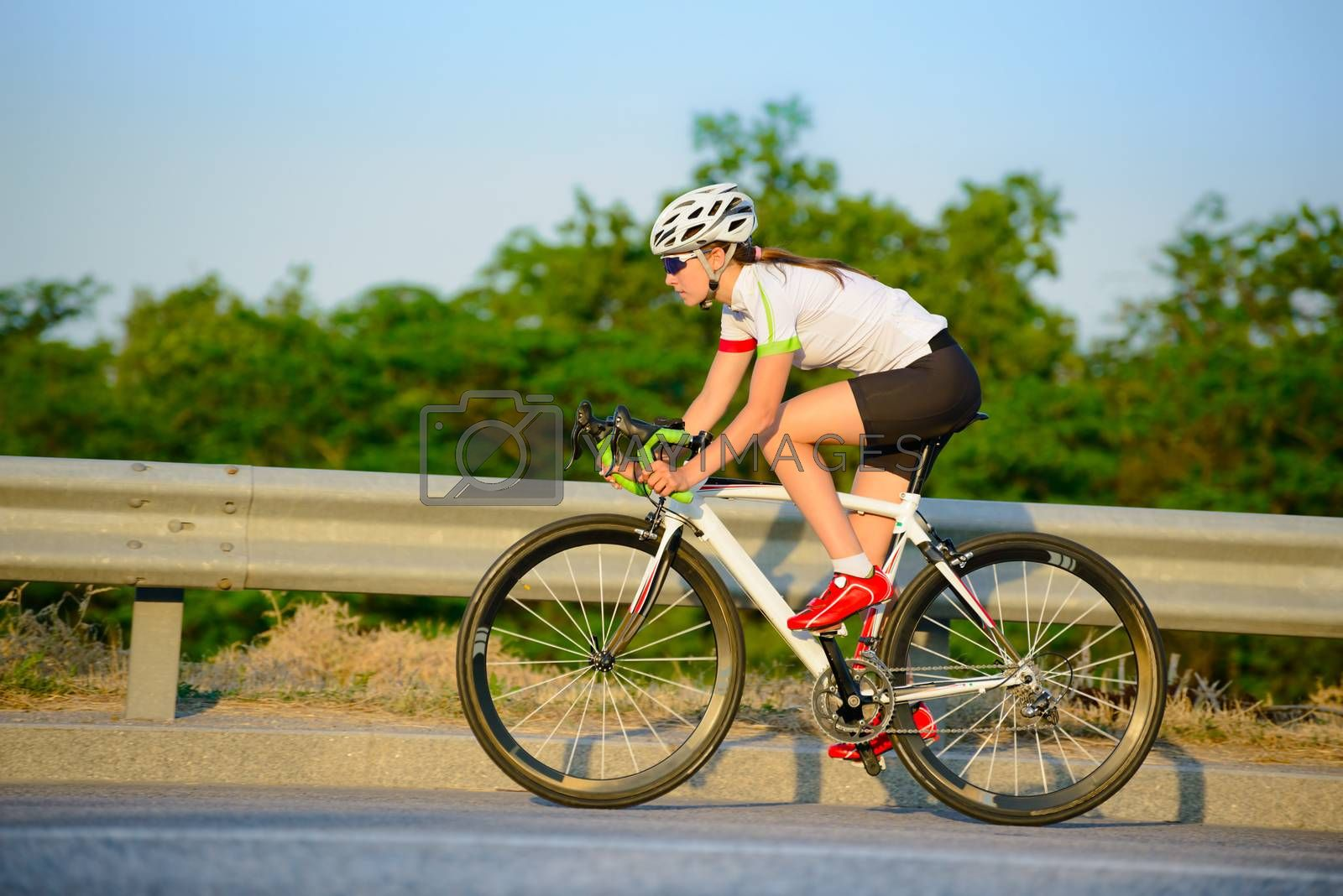 Young Woman Cyclist Riding Road Bicycle Uphill on the Highway in the Mountains at Summer Sunset. Healthy Lifestyle and Urban Sport Concept.