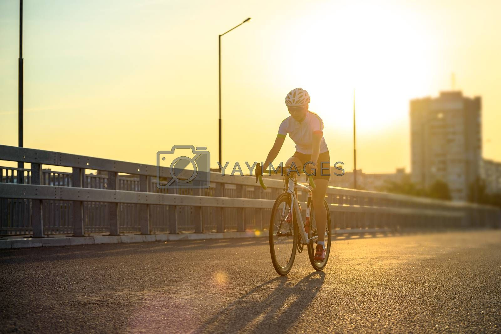 Young Woman Cyclist Riding Road Bicycle on the Free Street in the City at Hot Summer Sunset. Healthy Lifestyle and Urban Sport Concept.