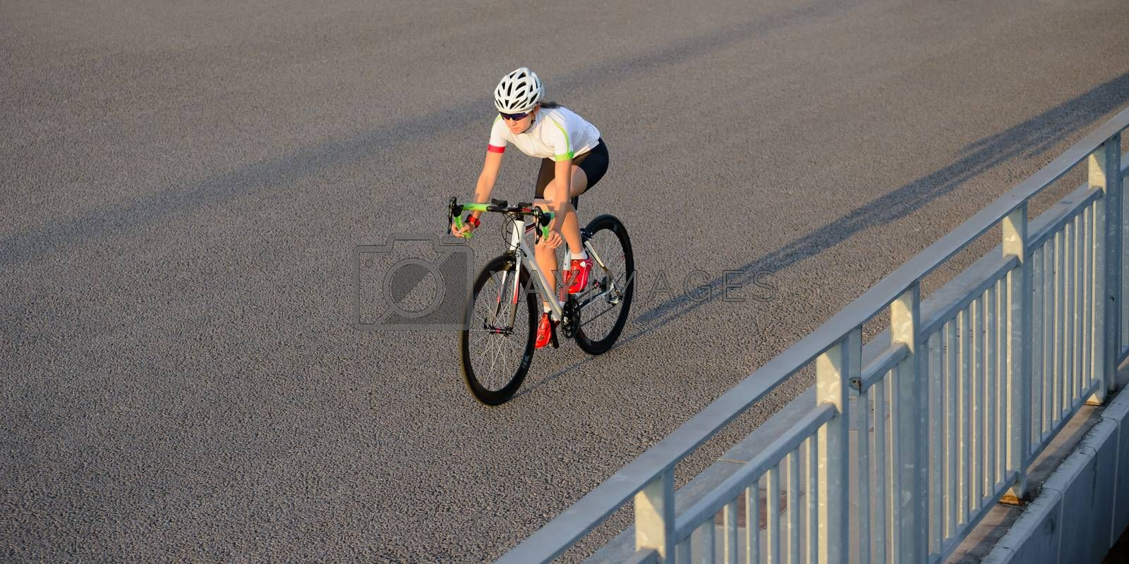 Young Woman Riding Road Bicycle on the Bridge in the City at Sunset. Healthy Lifestyle and Sport Concept. by maxpro