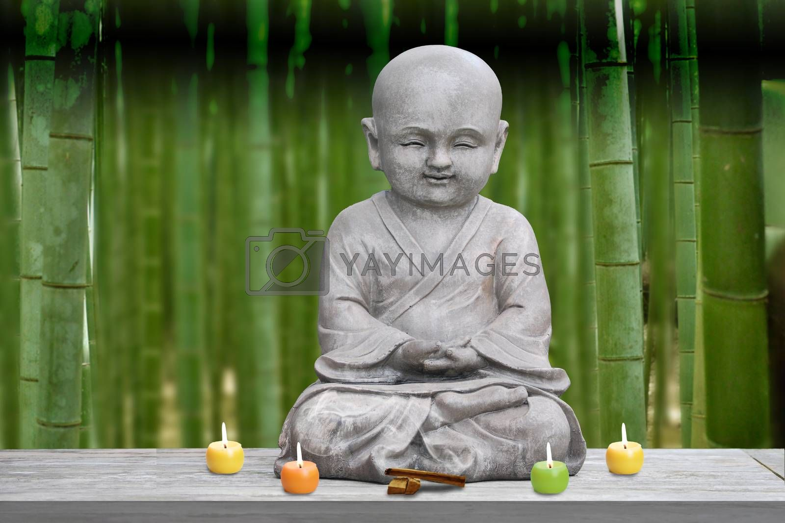 Buddha stone statue child bamboo background blur lit candles and incense