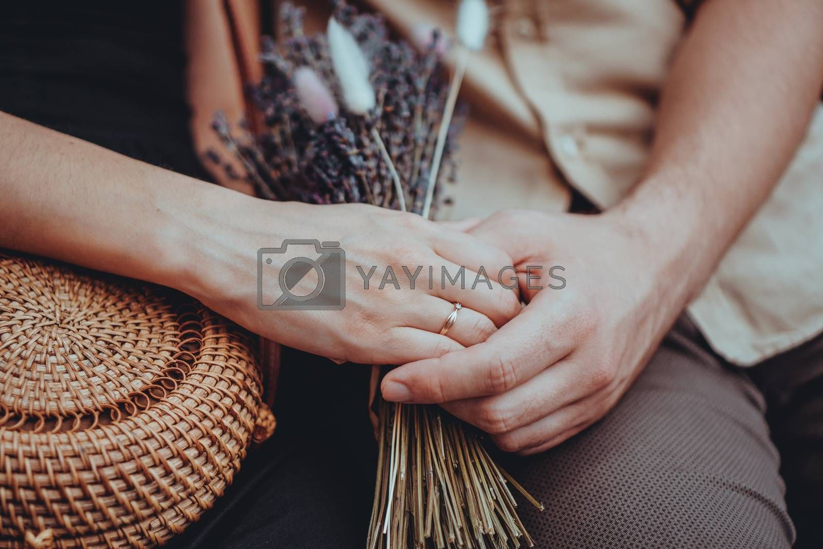 Bouquet of lavender flowers in girls hands. Engagement ring on hand. Love couple holding hands. Love, relationships, travel, romance concept.