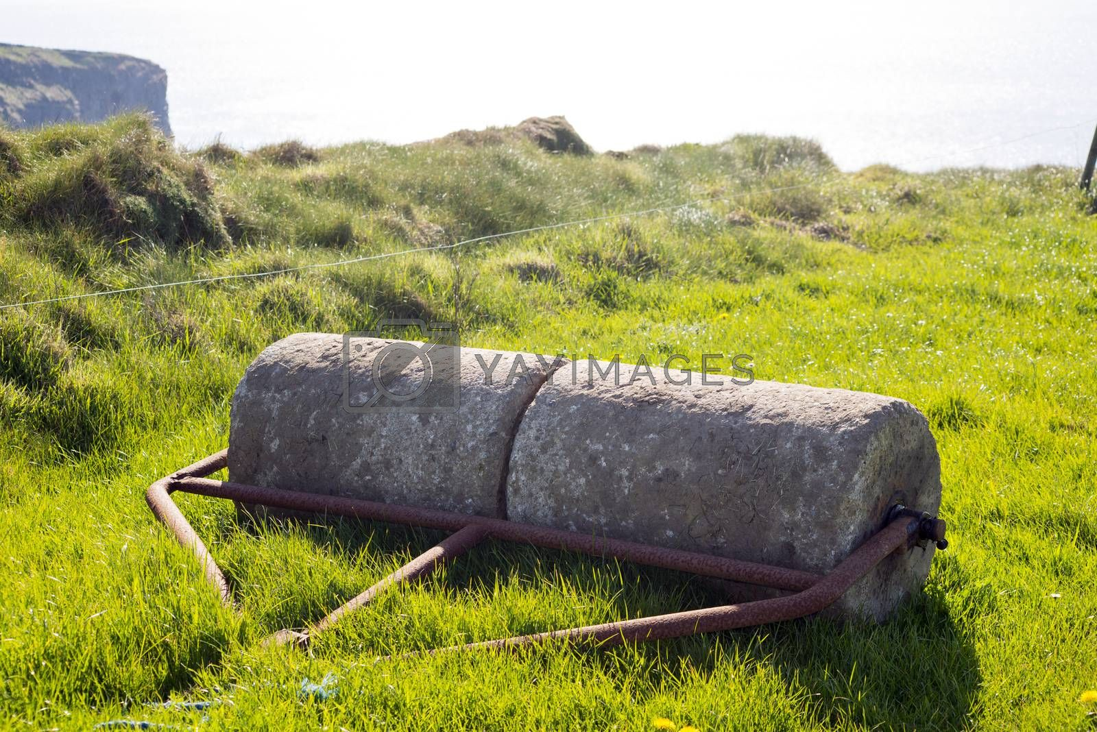 old rustic concrete roller abandoned at a field in ireland