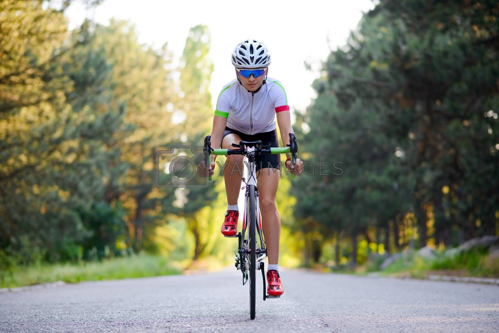 Young Woman Cyclist Riding Road Bicycle on Free Road in the Forest at Hot Summer Day. Healthy Lifestyle Concept.