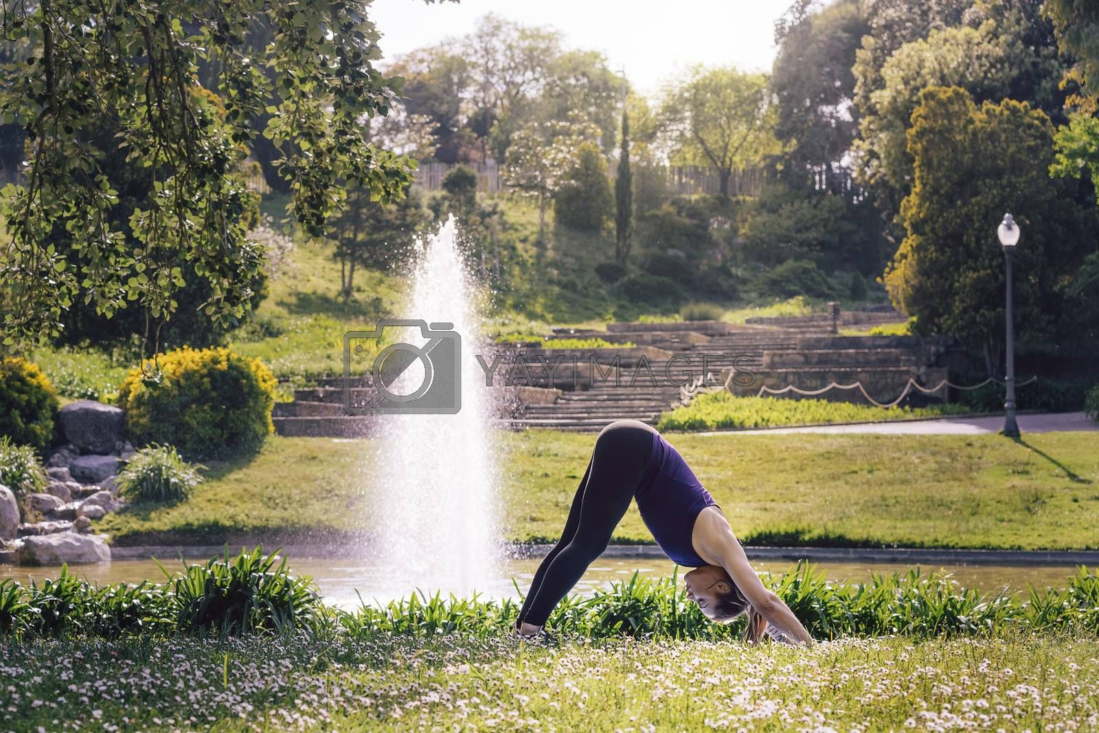 woman doing yoga outdoors in the park by raulmelldo