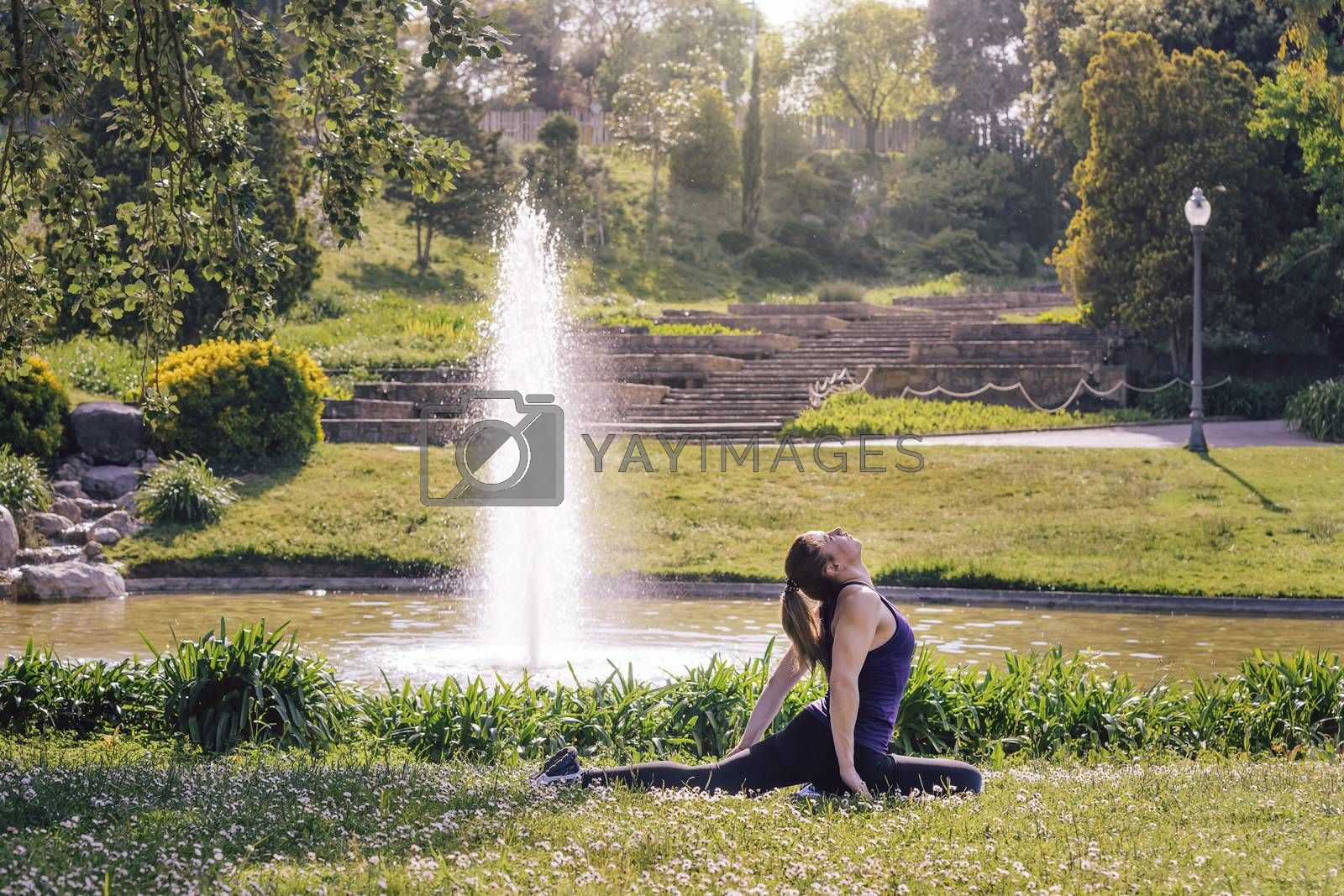 young sporty girl doing meditation yoga exercises and relaxing outdoors in the park, modern healthy lifestyle and sport concept