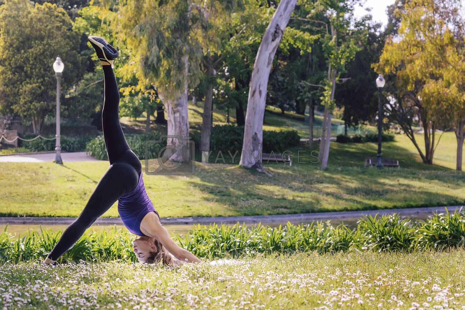 young sports woman doing meditation yoga balancing exercises and relaxing outdoors in the park, modern healthy lifestyle and sport concept