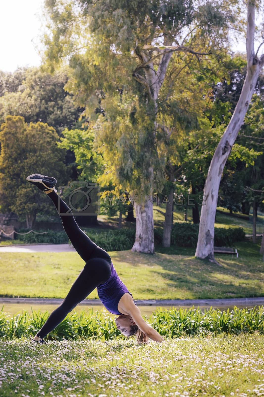 vertical photo of a young sports woman doing meditation yoga balancing exercises and relaxing outdoors in the park, modern healthy lifestyle and sport concept