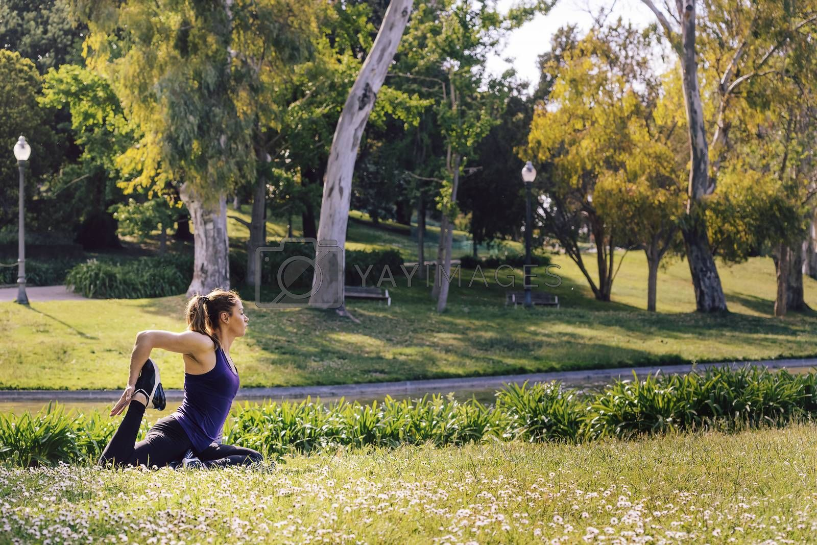 young woman doing yoga exercises in the nature by raulmelldo