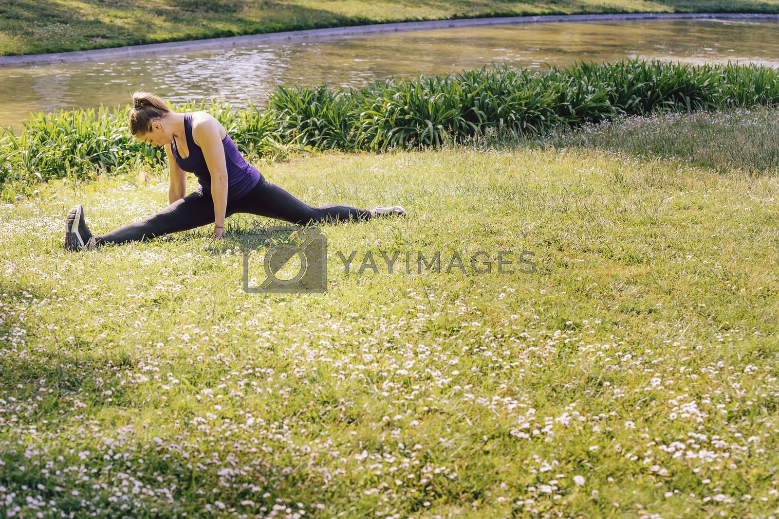 young sports woman doing flexibility exercises and stretching legs on the grass outdoors in the park, modern healthy lifestyle and sport concept, copy space for text
