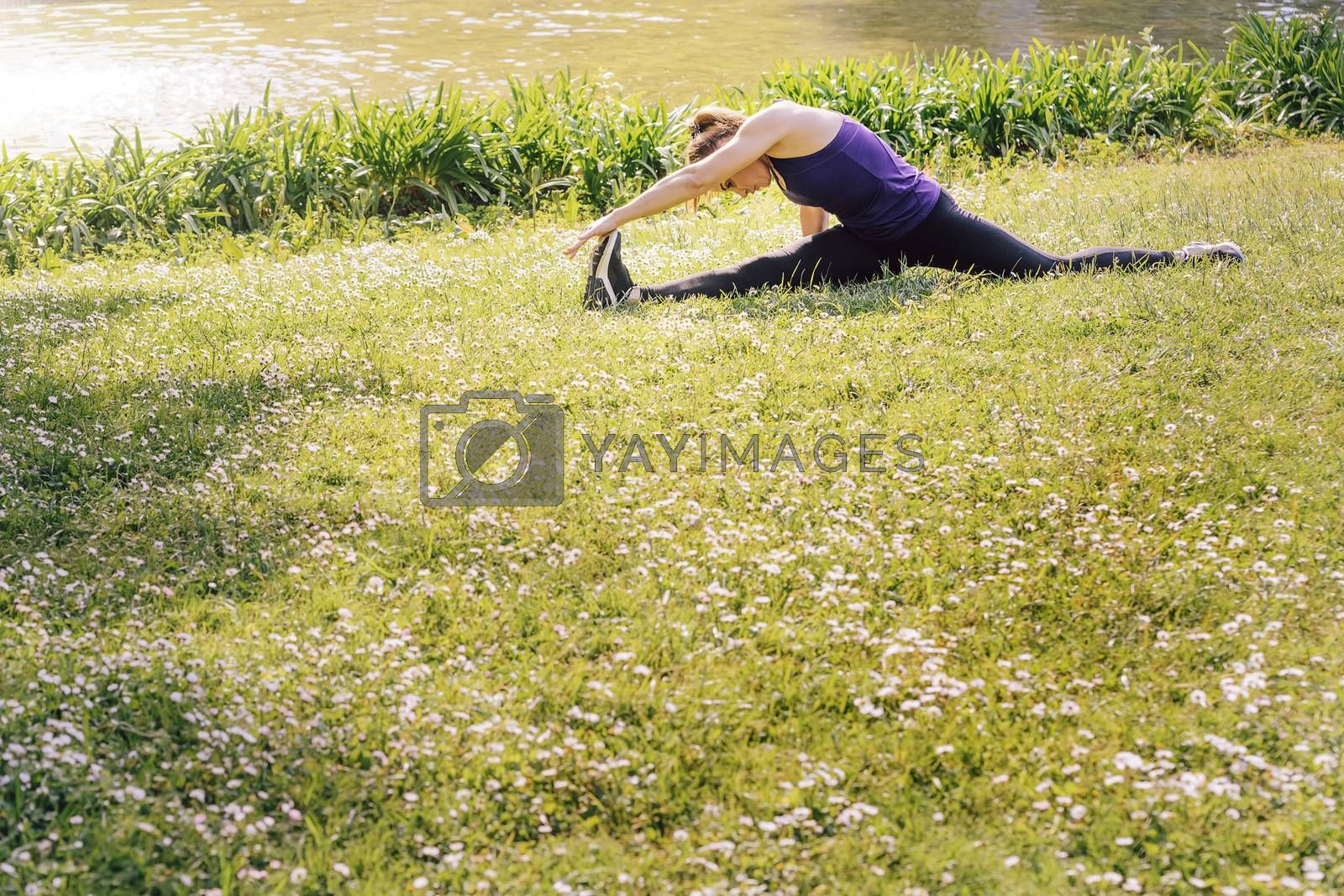 young sporty woman doing flexibility exercises and stretching legs on the grass outdoors in the park, modern healthy lifestyle and sport concept, copy space for text
