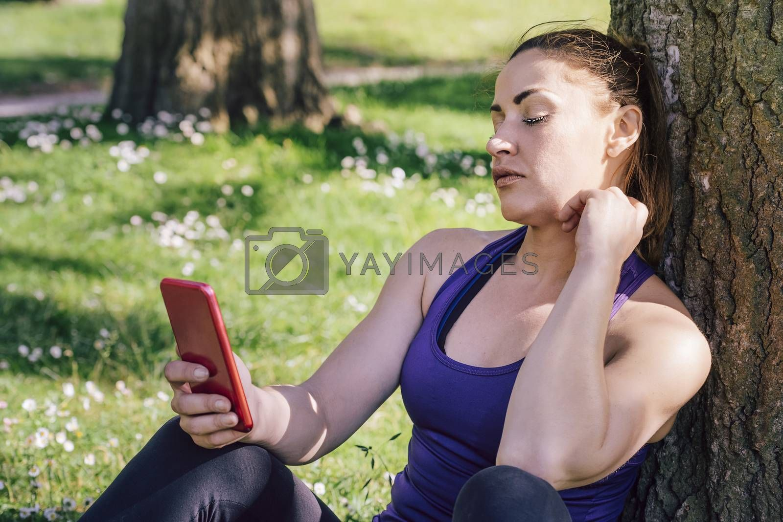 sports woman looking at her phone while resting after exercise sitting next to a tree, healthy modern lifestyle and sport concept