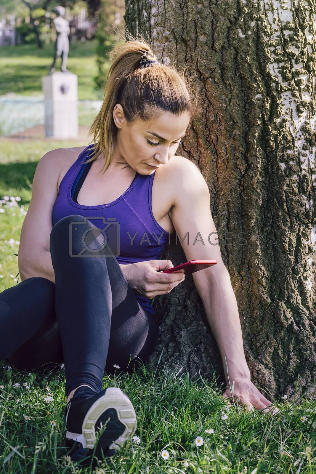 sports woman taking a look to her phone while resting after exercise sitting next to a tree, healthy modern lifestyle and sport concept