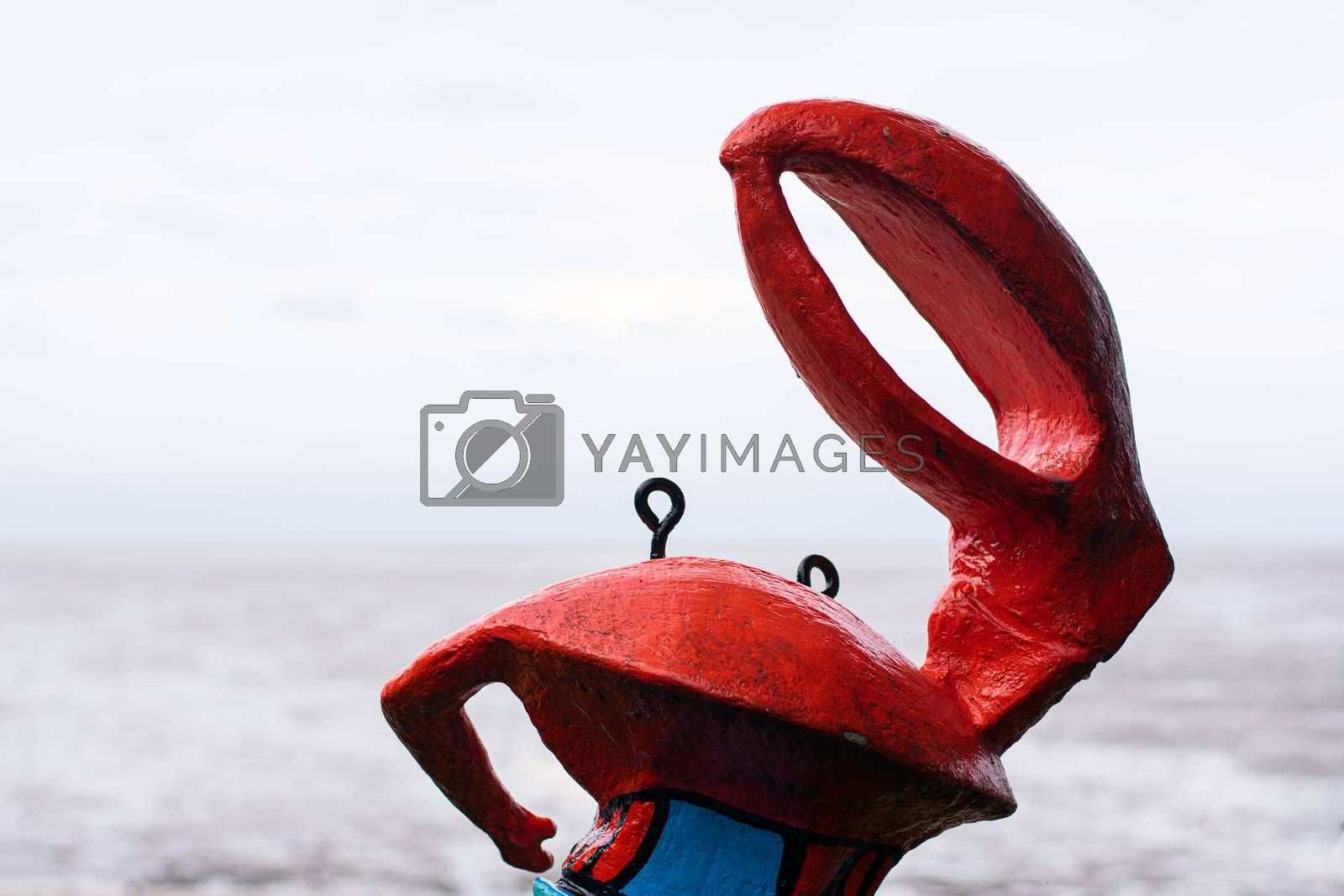Red crab statue on sandy beach