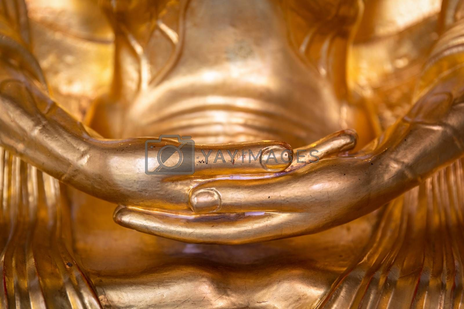 Close focus on hands of golden buddha statue.