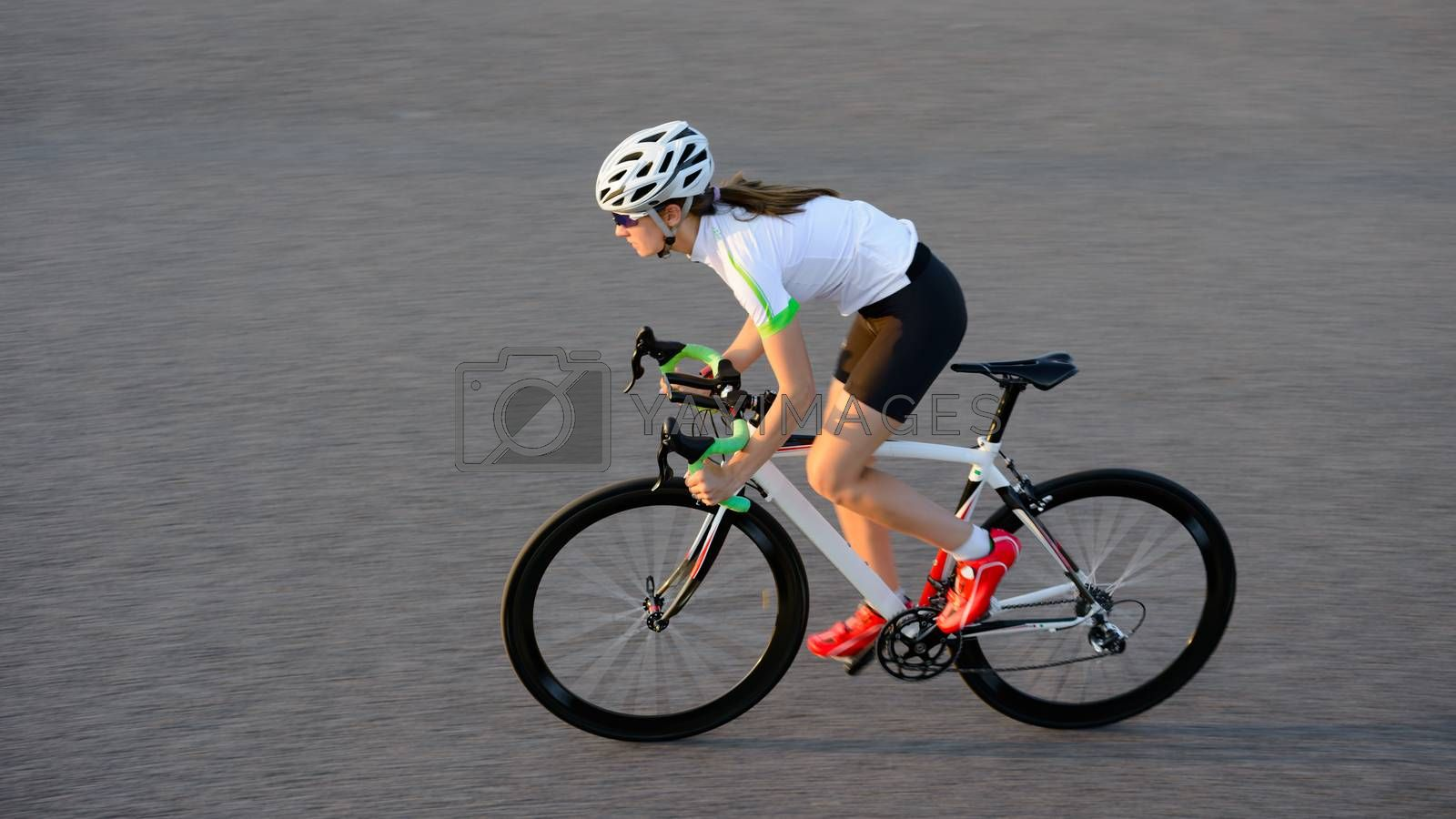 Young Woman Cyclist Riding Road Bicycle on the Free Street in the City at Summer Sunset. Healthy Lifestyle and Urban Sport Concept.