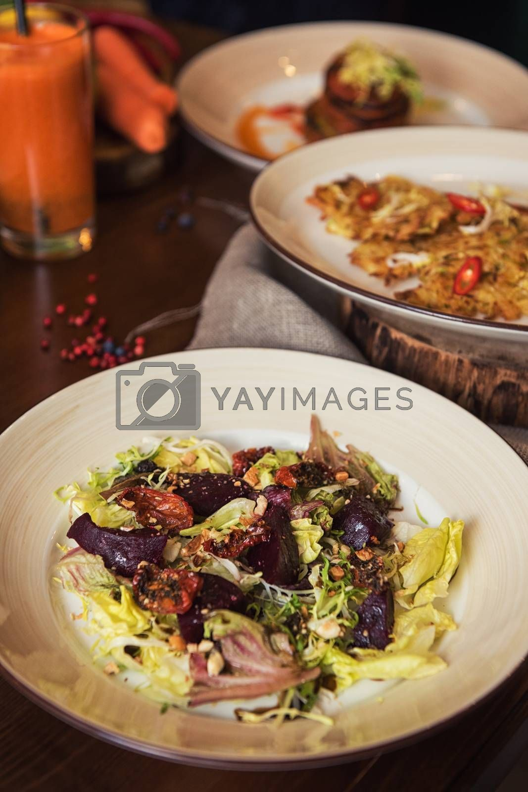 Healthy vegeterian food on brown wood board. Spring vitamin dieting food. Salad from beet with dried tomatoes and cabbage