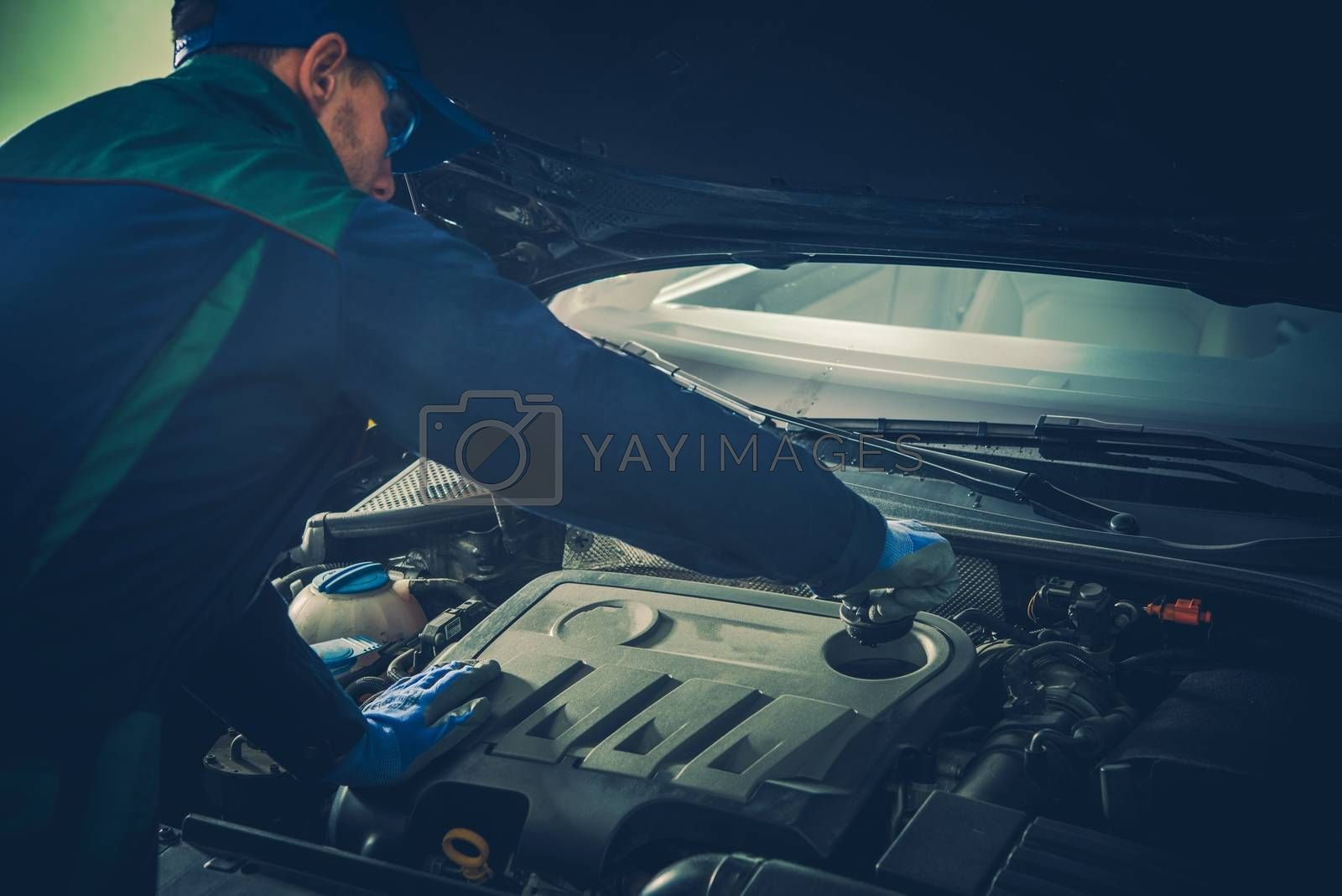 Vehicle Fluids Maintenance by Professional Car Mechanic. Caucasian Service Technician in His 30s.
