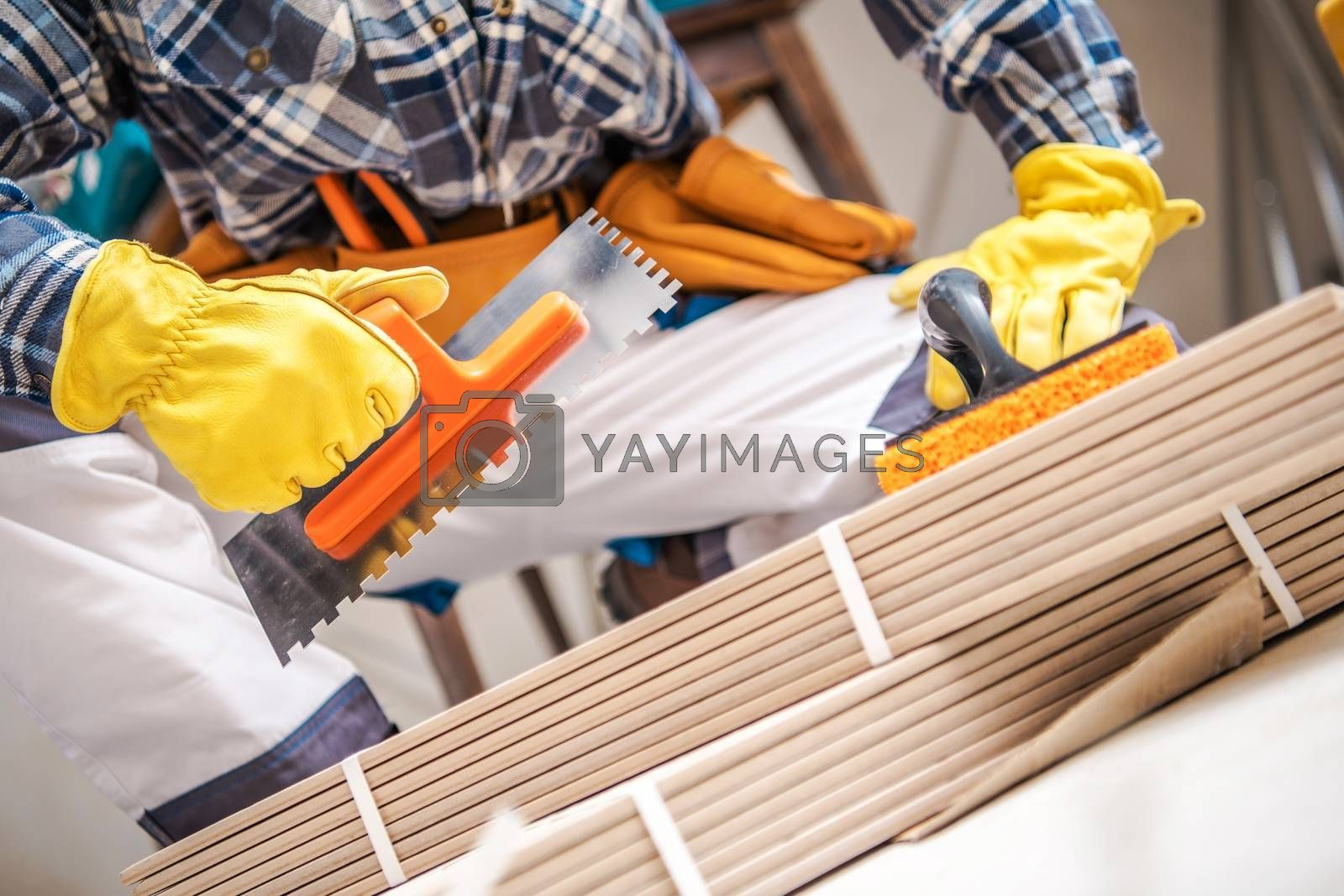 Ceramic Tiles Installer with Construction Tools. Closeup Photo.