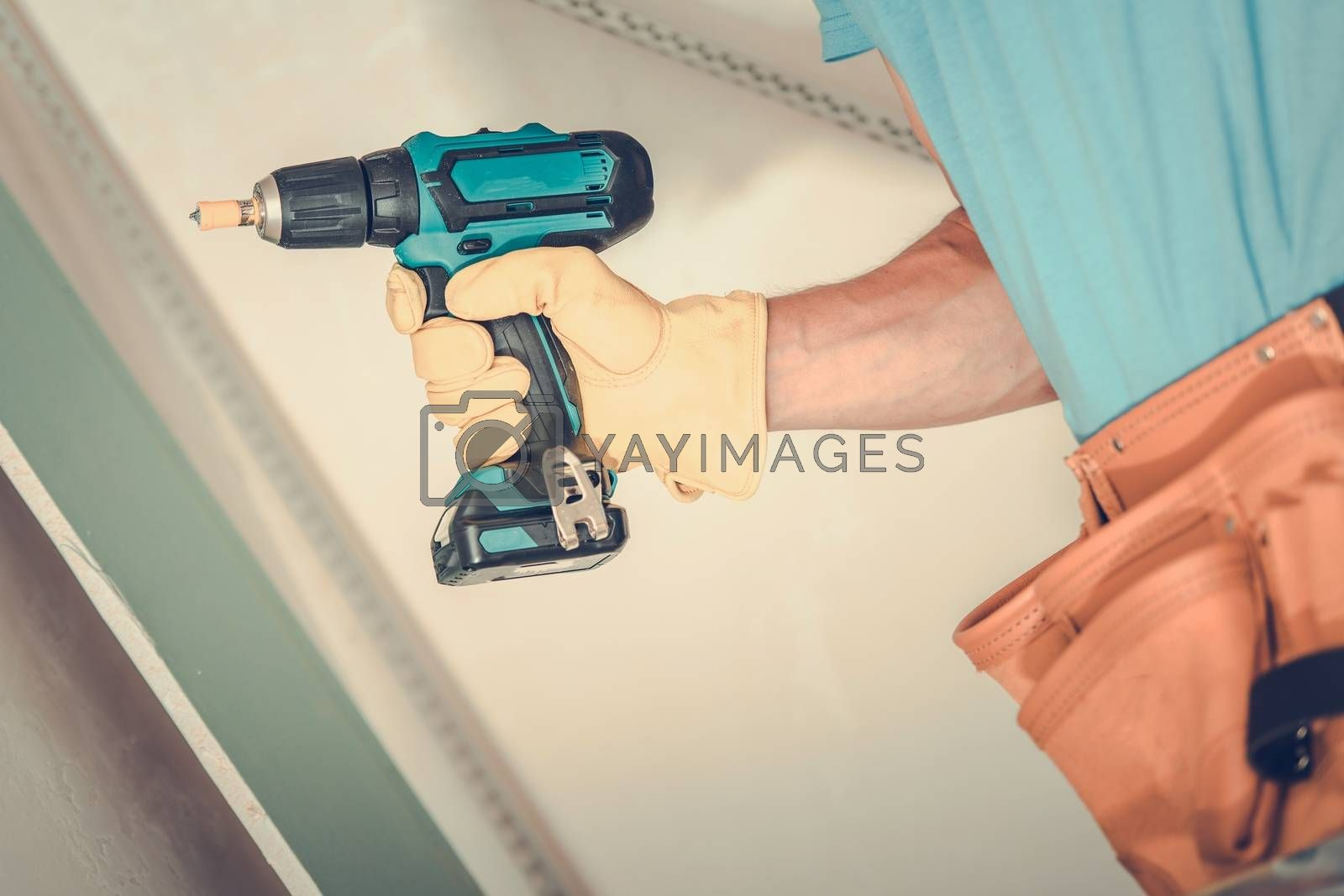 Drywall Building. Contractor with Drill Driver Closeup Photo. Construction Theme.