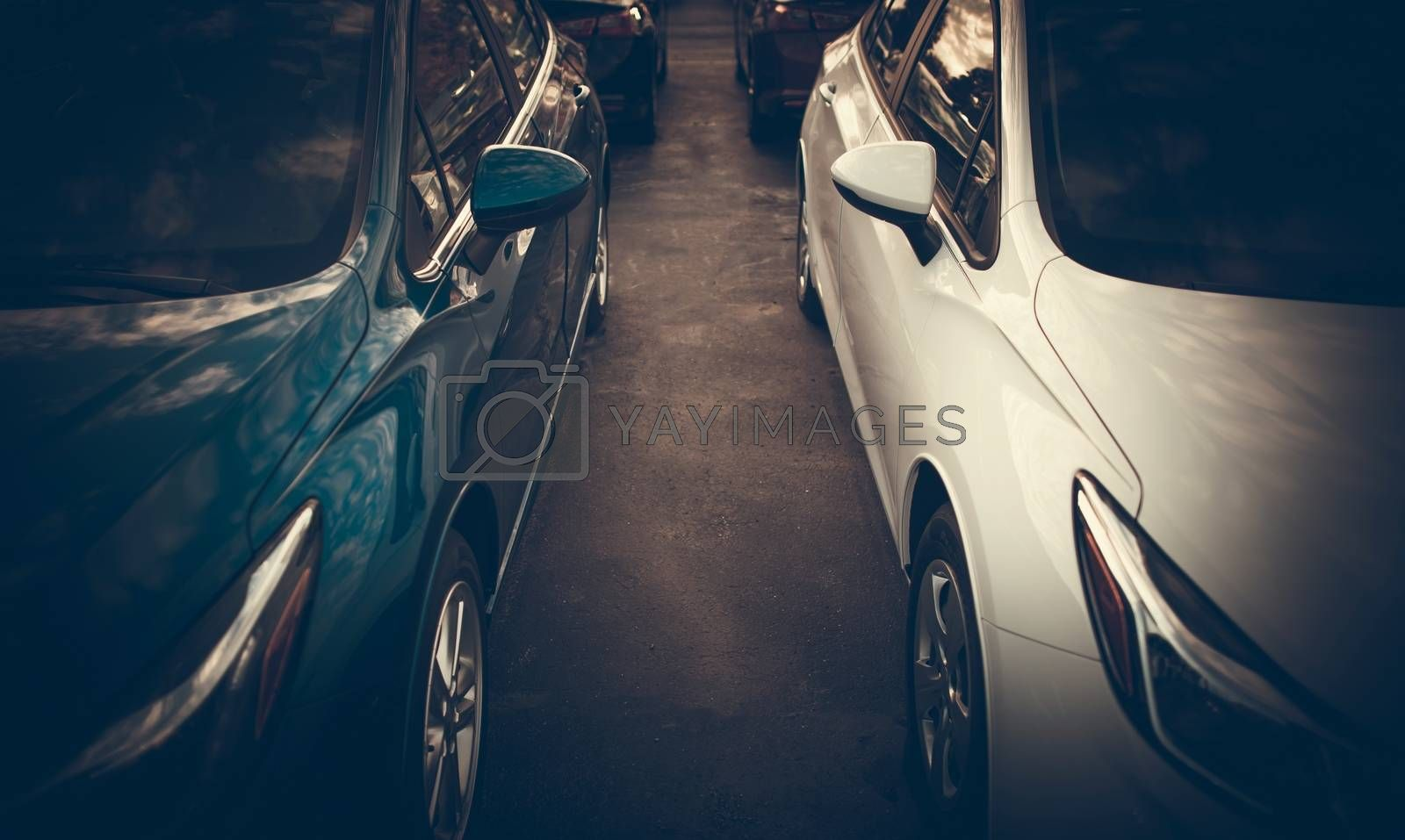 Tight Car Parking Spaces Theme. Modern Vehicles Side by Side Closeup Photo.