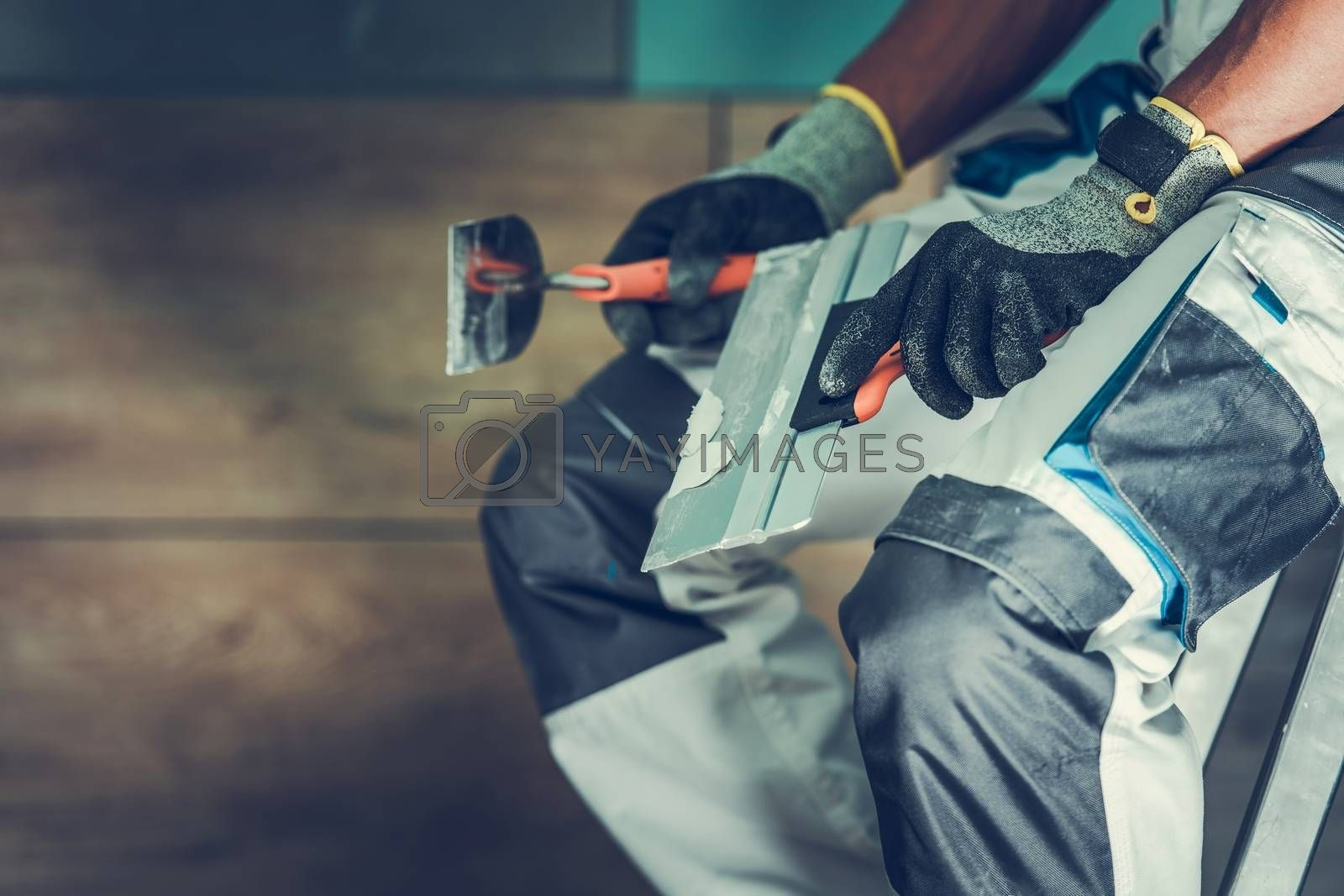 Tiles Installer Contractor with Tools. Closeup Photo. Construction Theme.
