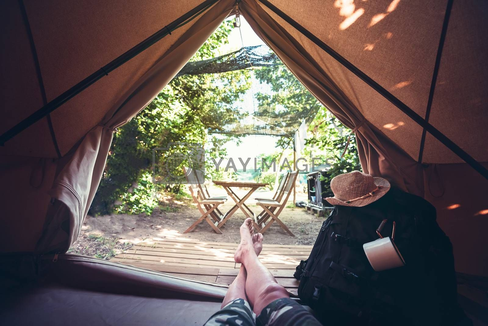 view of crossed legs of a hiker man resting barefoot in a camping tent, travel discovery concept, point of view shot