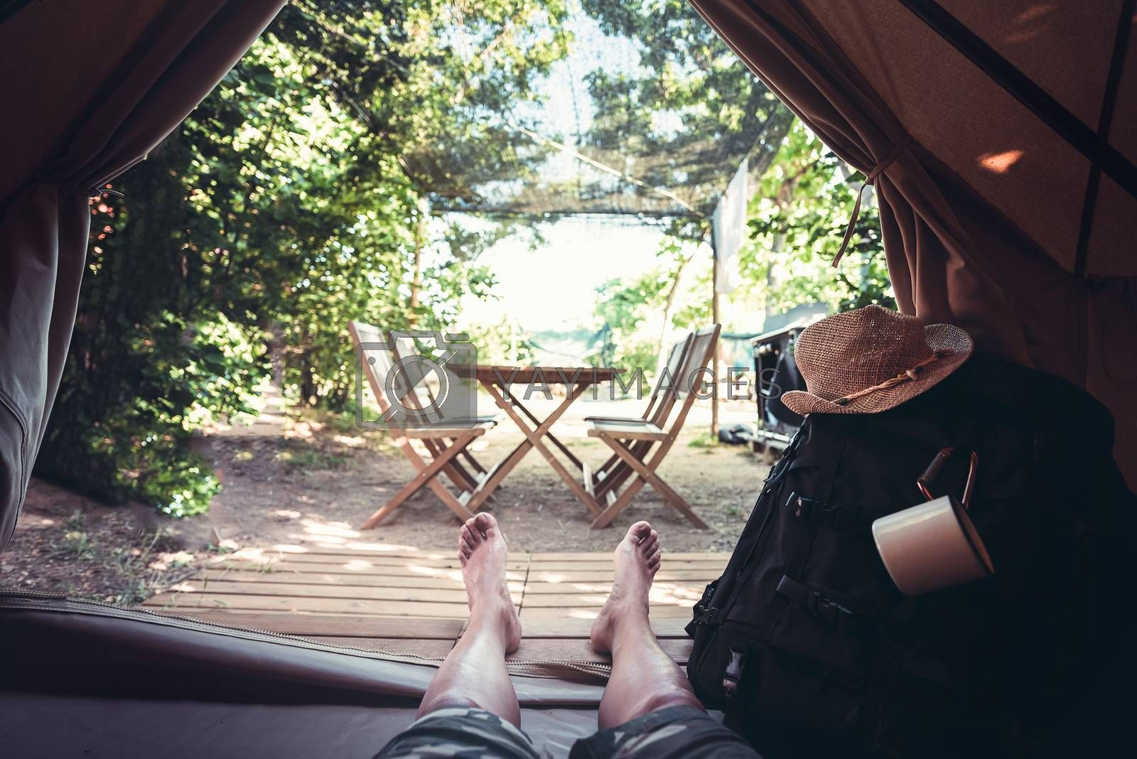 view of legs of a hiker man resting barefoot in a camping tent, travel discovery concept, point of view shot