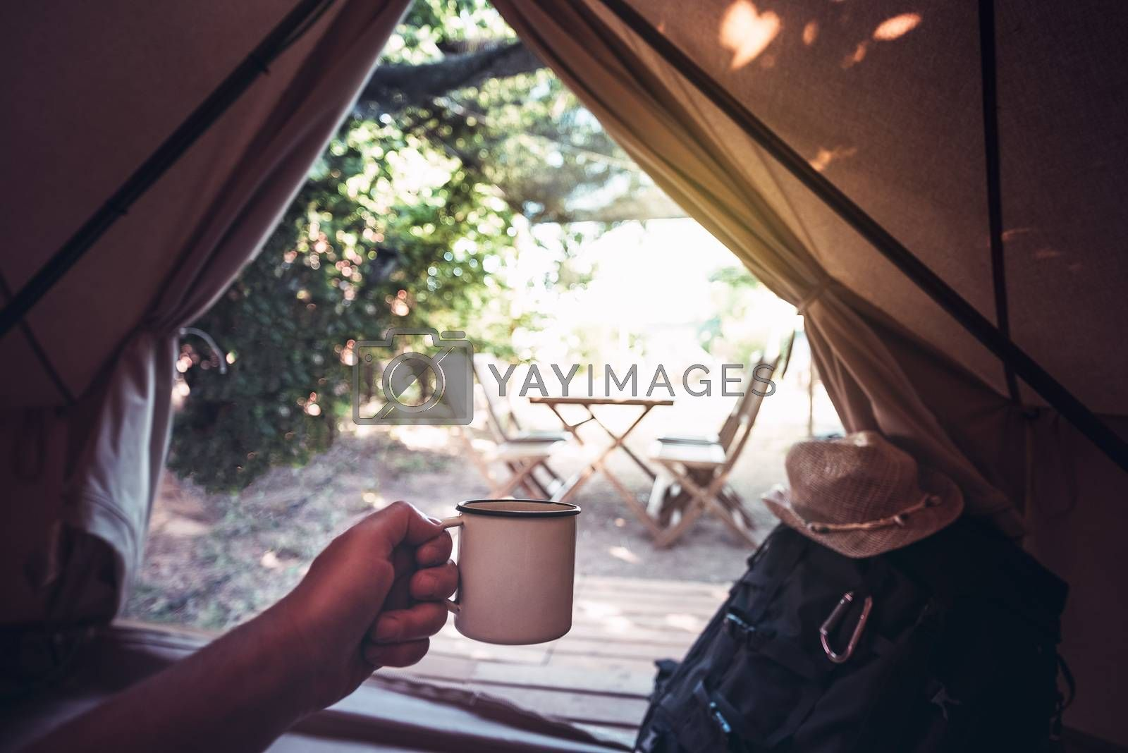 view of a hand of a hiker person resting with a cup in a camping tent, travel discovery concept, point of view shot