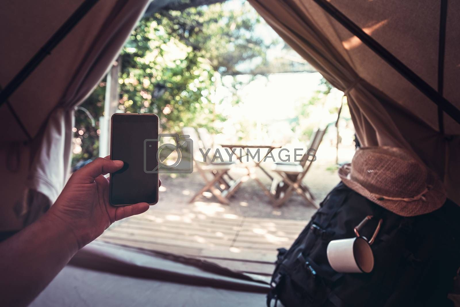 view of a hand of a hiker person resting while consulting the phone in a camping tent, travel discovery concept, point of view shot