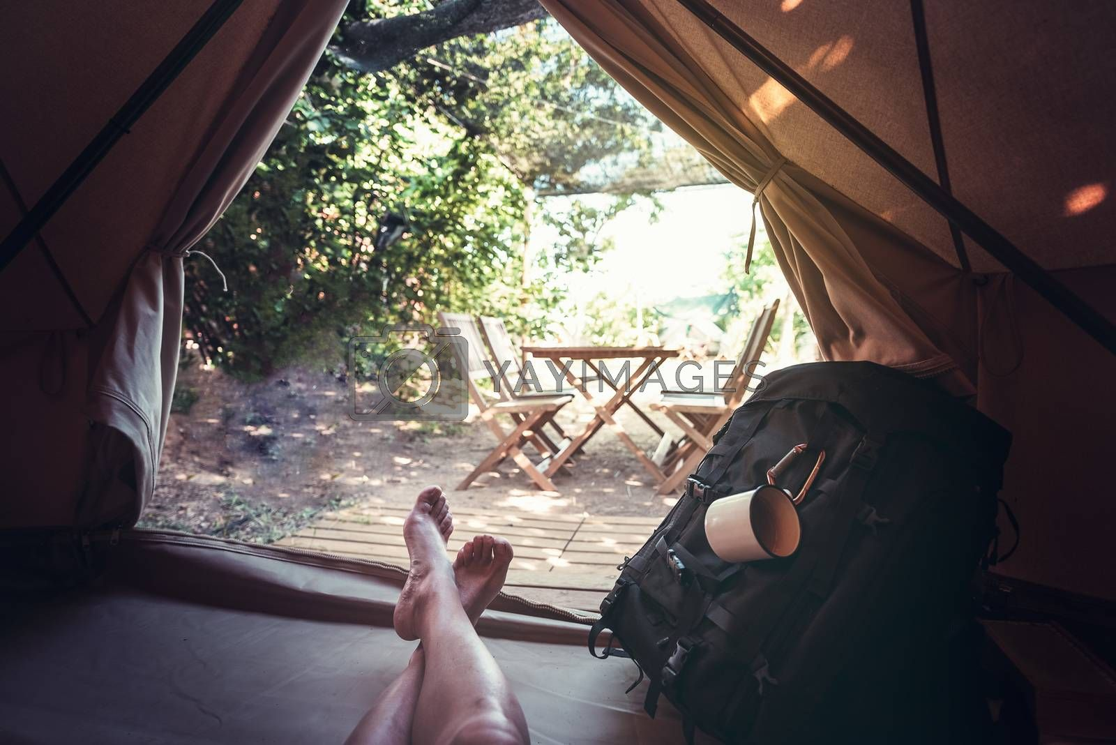 view of crossed feet of a hiker person resting barefoot in a camping tent, travel discovery concept, point of view shot