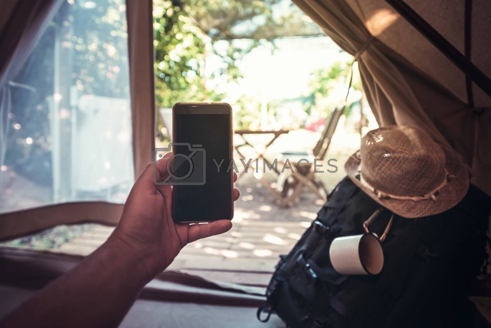 view of a hand of a hiker man resting while consulting the phone in a camping tent, travel discovery concept, point of view shot