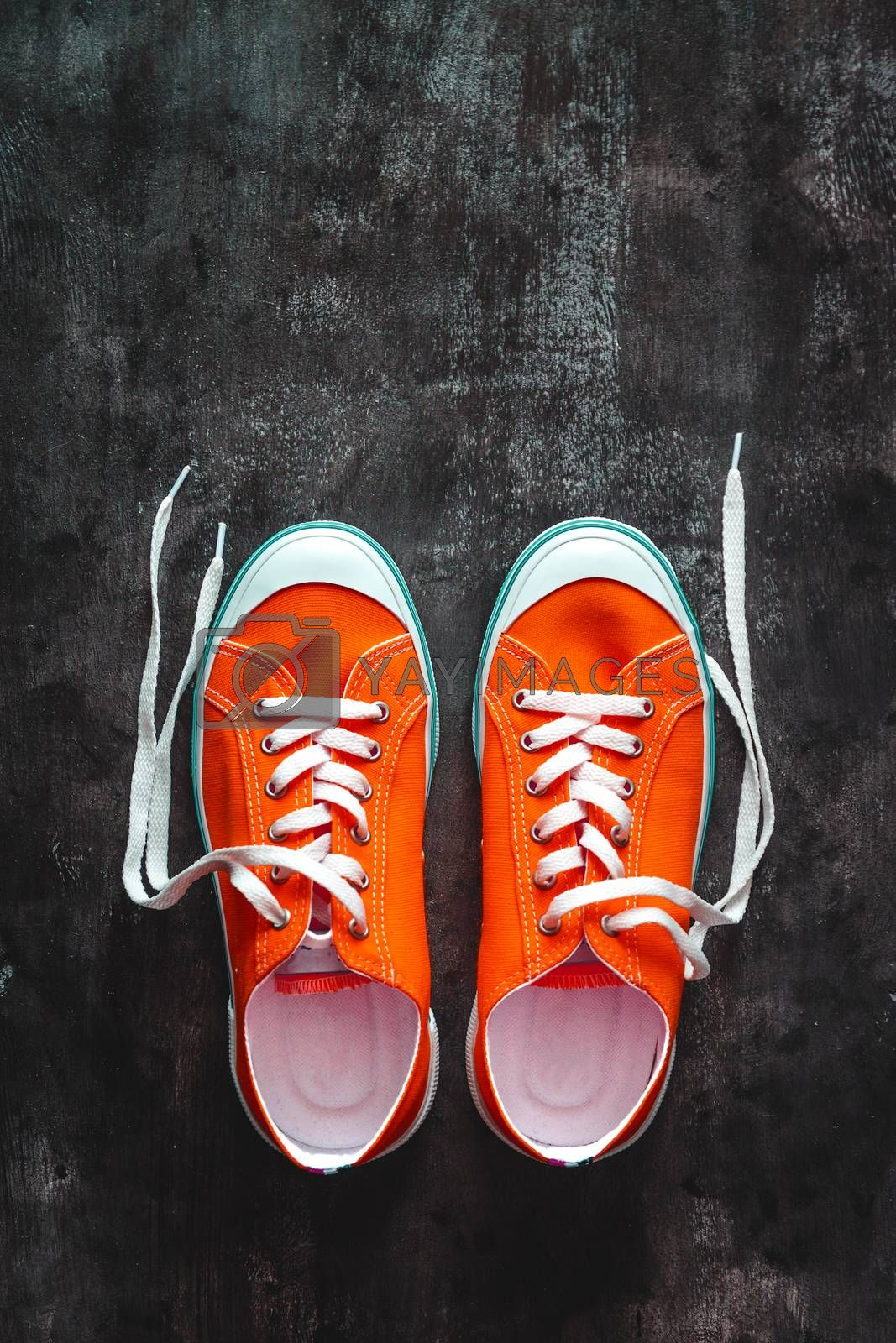 Royalty free image of red sneakers with untied laces on a dark concrete background. Co by Tanacha