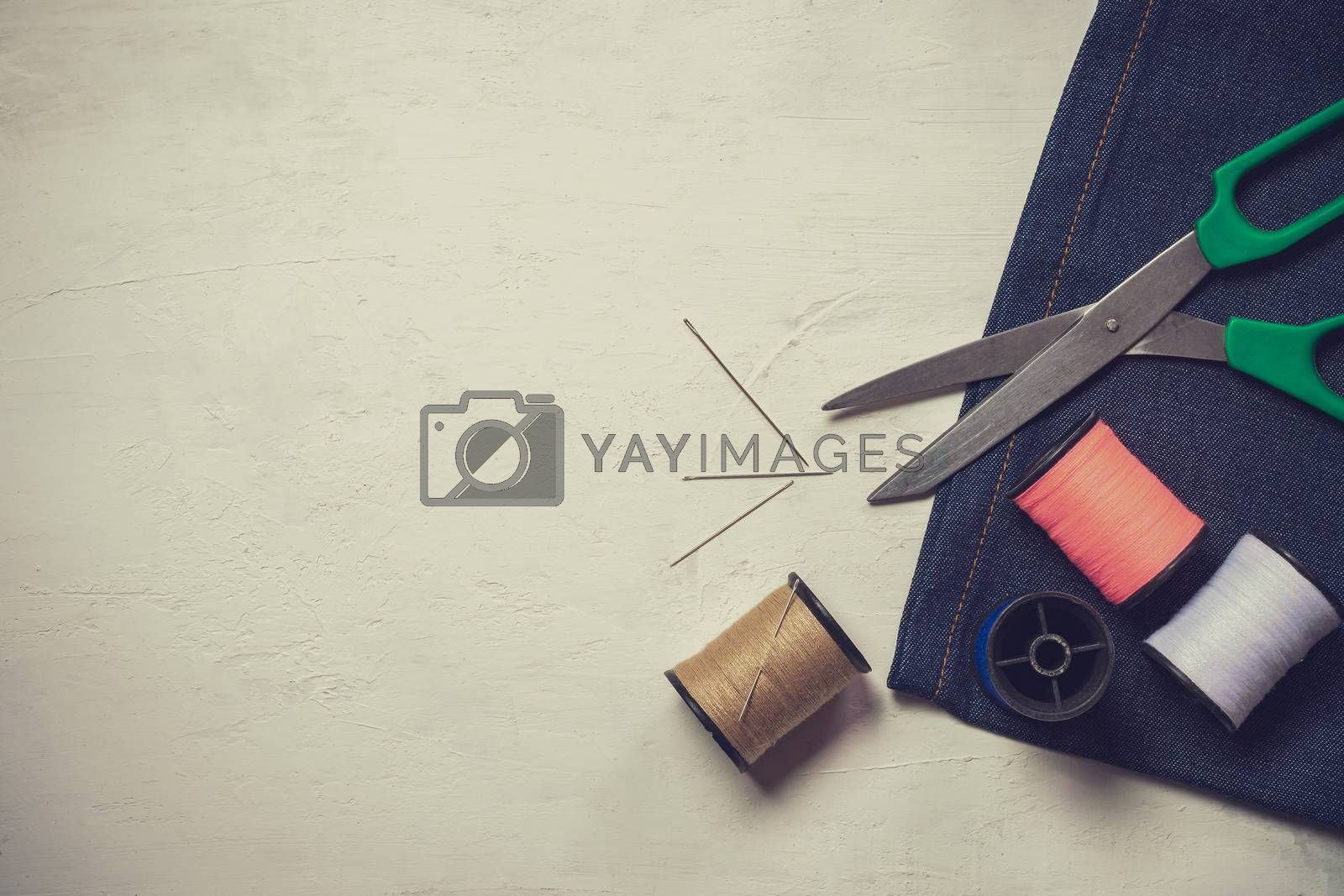 Royalty free image of Sewing tools and equipment on white wooden floor. Top view and c by SaitanSainam
