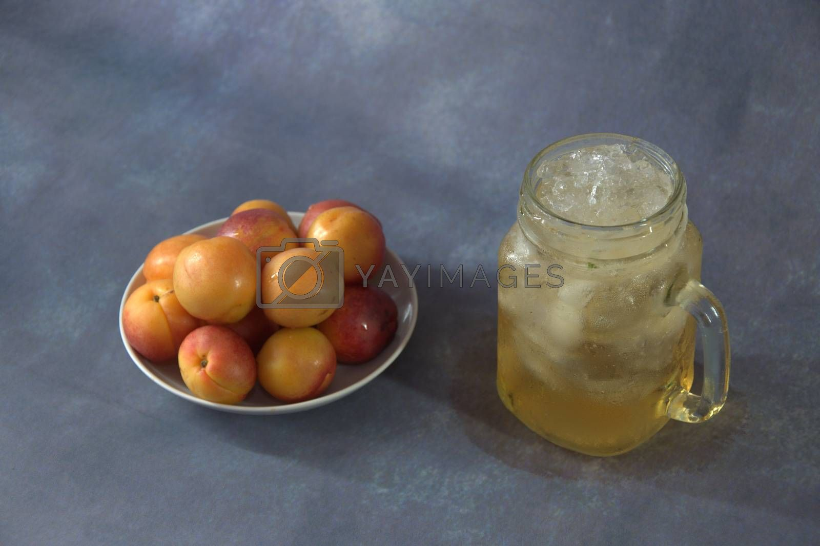 Royalty free image of A glass mug with a refreshing juice with ice and a full plate with ripe apricots. Close-up. by alexey_zheltukhin