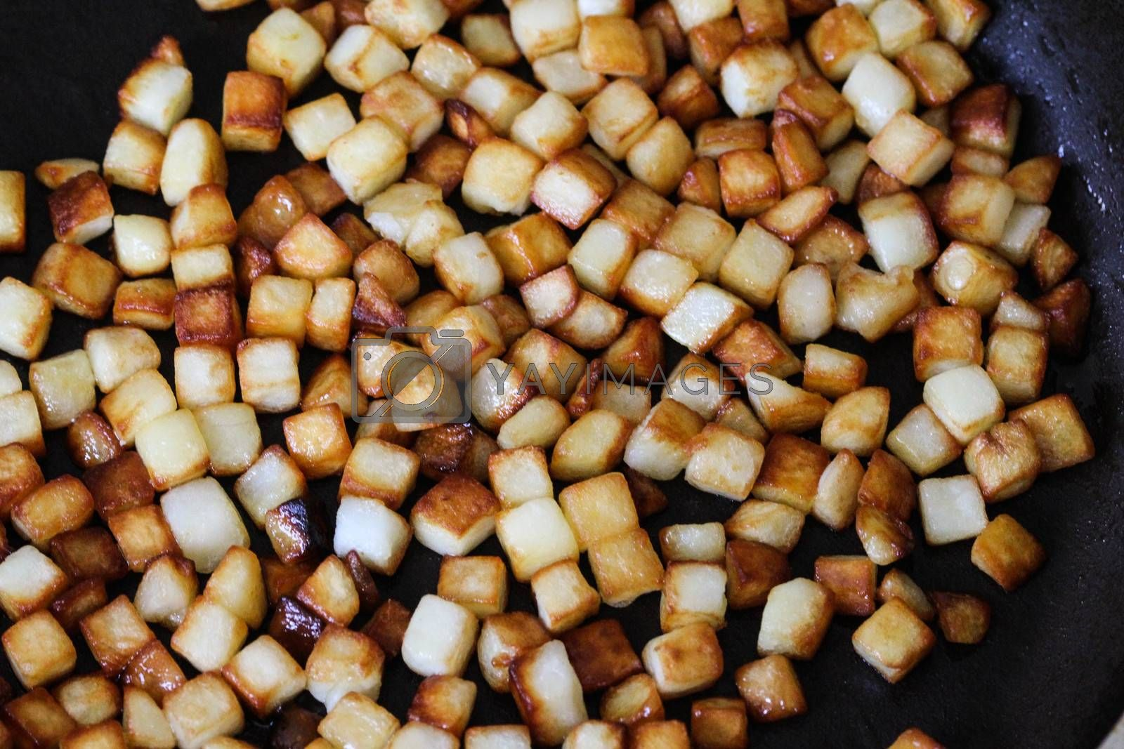 Royalty free image of baked potato cubes in pan in kitchen by michaelmeijer