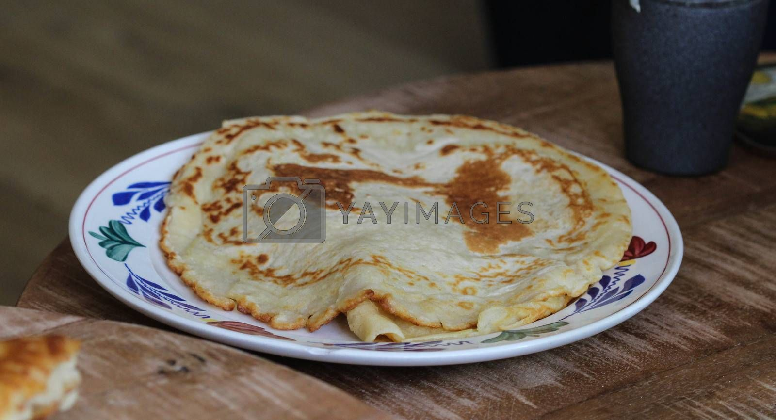 Royalty free image of Fresh self baked natural empty pancakes on a white plate on a wooden background by michaelmeijer