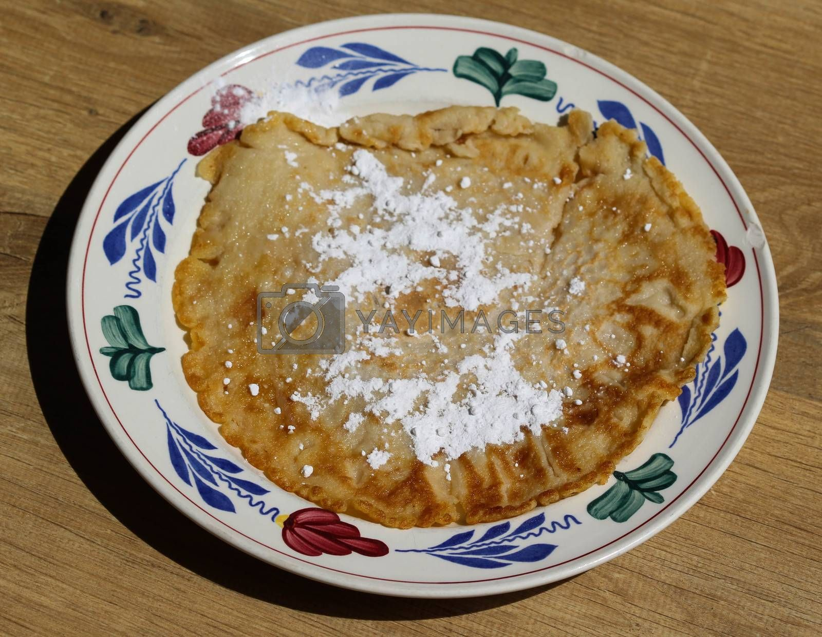 Royalty free image of fresh baked pancake with powdered sugar on plate on wooden background by michaelmeijer