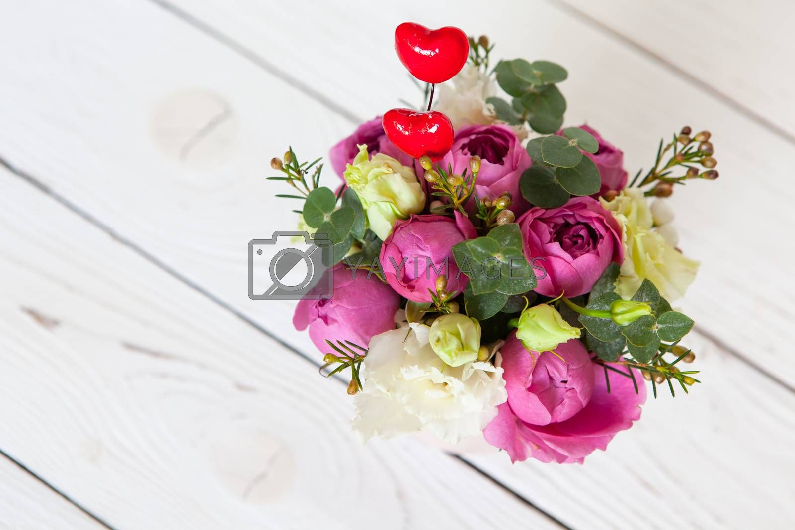 Creative flower bouquet on white wooden background. Focus on flowers, background is blurred. Copy space. For greeting card, social media, flower delivery, Mother's day, Women's Day