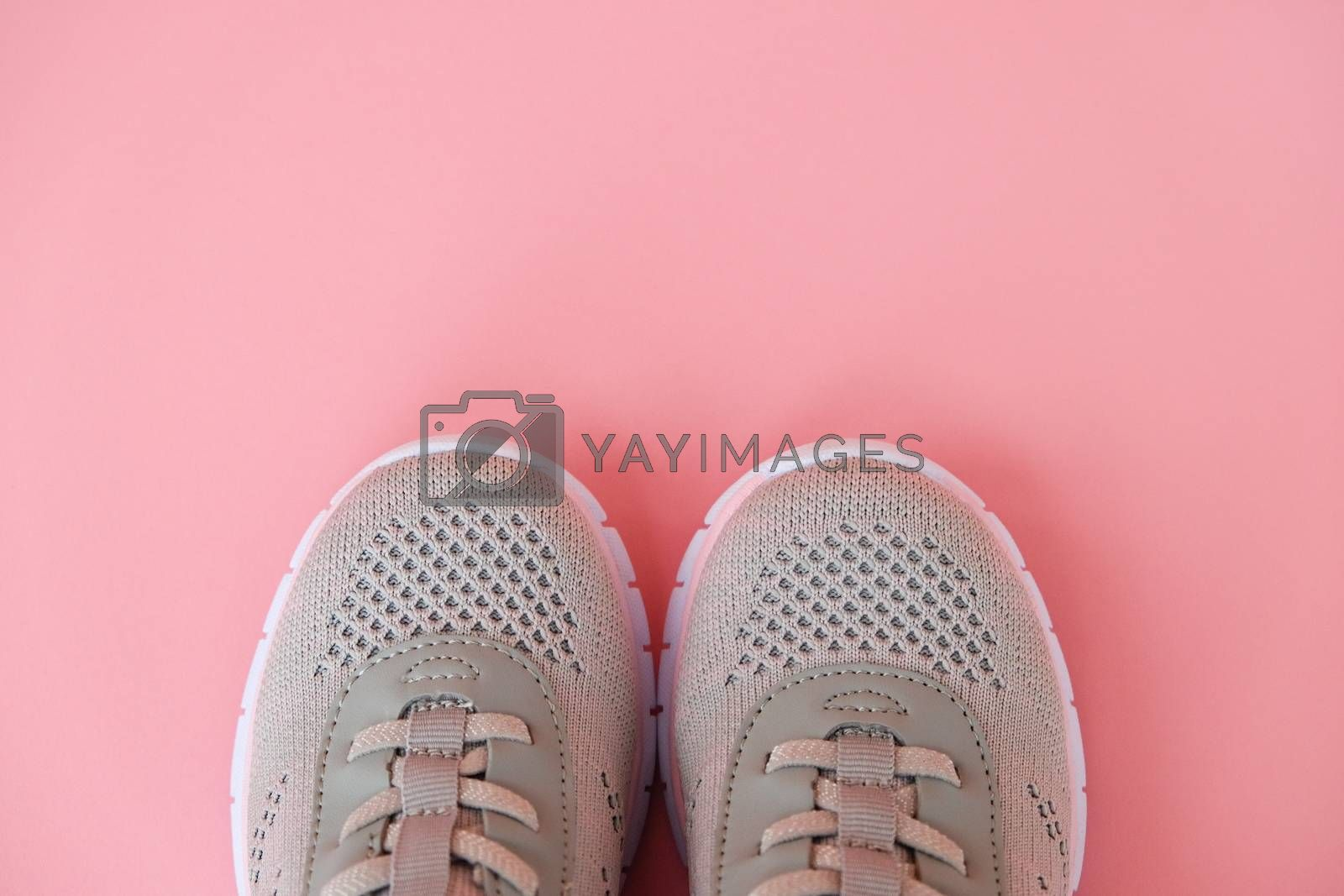 Sport, healthy lifestyle concept. New gray sneakers on pastel pink background. Copy space. Flat lay. Close-up.